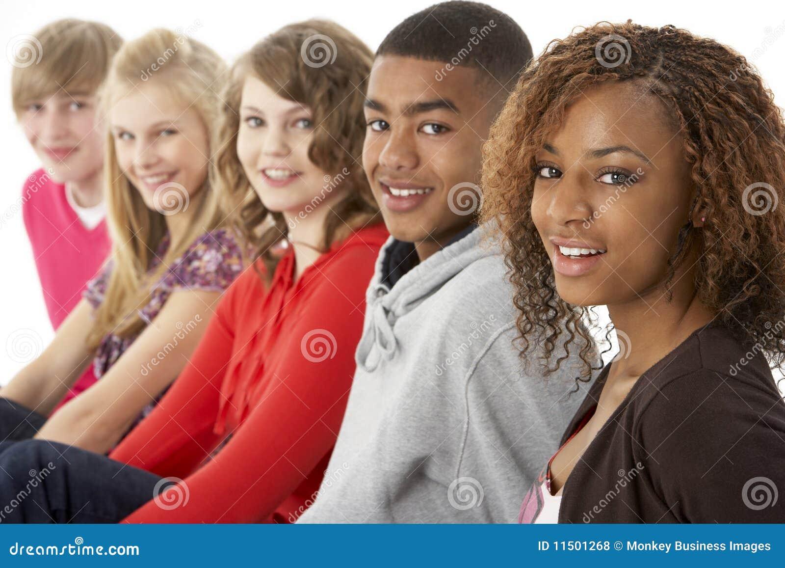 Un ritratto dello studio di cinque amici adolescenti che si levano in piedi I