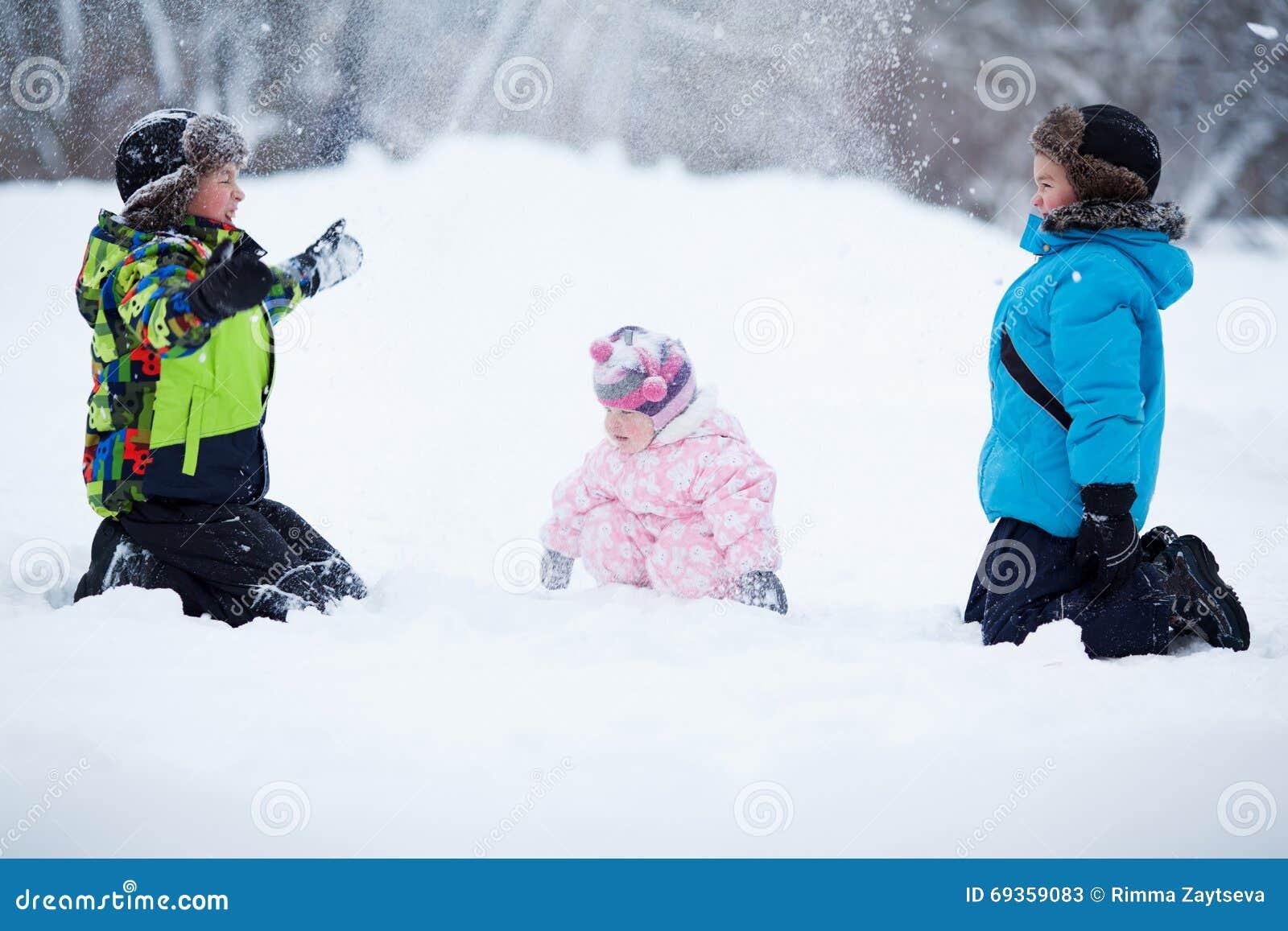 Un ritratto di due ragazzi felici allegri e la neonata nell inverno parcheggiano