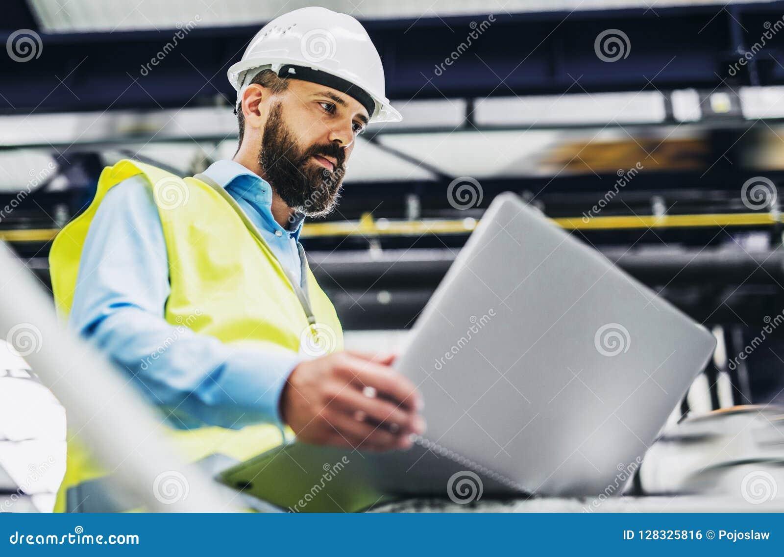 Un ritratto di un ingegnere industriale dell uomo con il computer portatile in una fabbrica, lavorante
