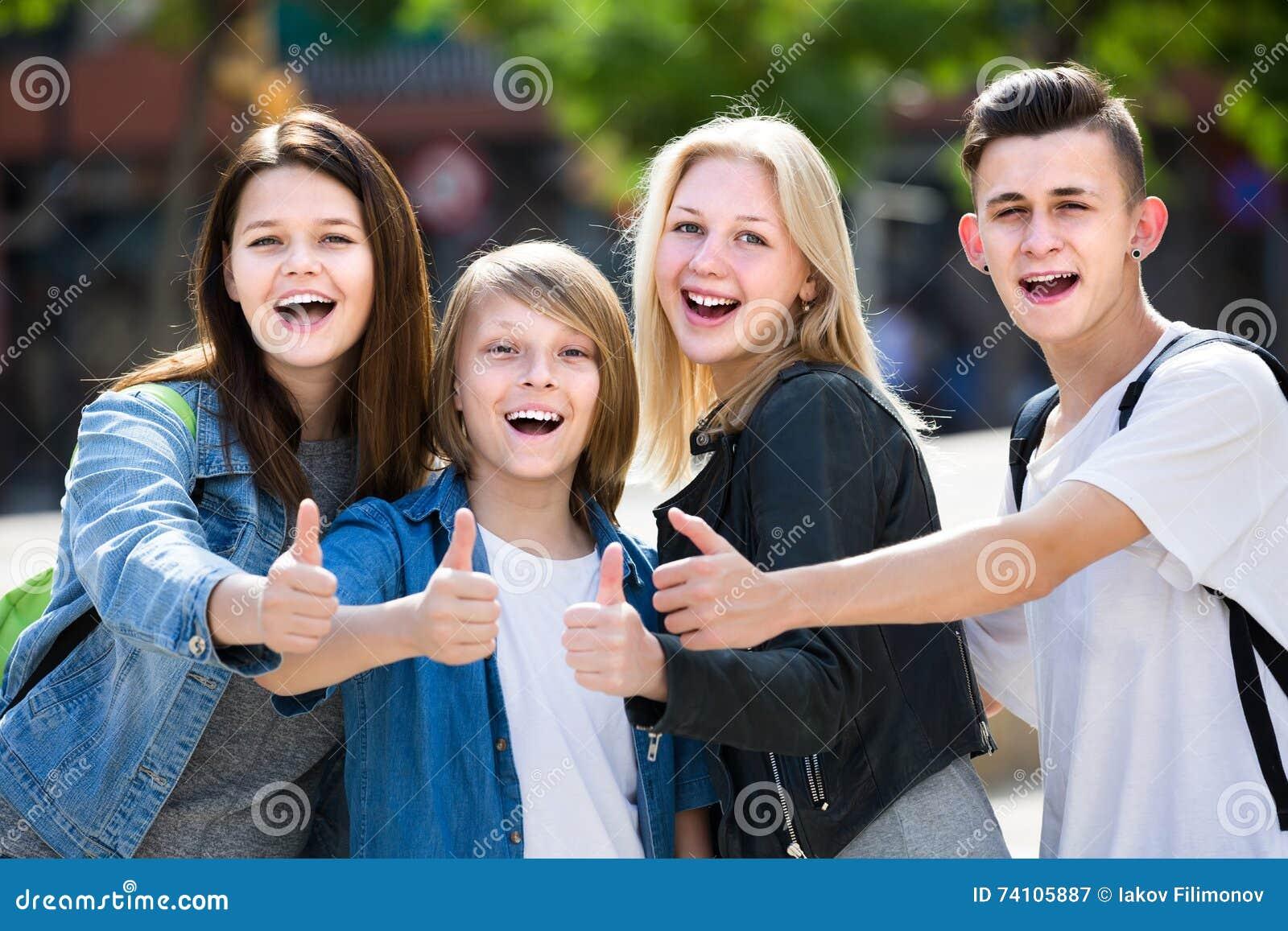 Un ritratto di quattro adolescenti che stanno e che tengono sfoglia su togeth