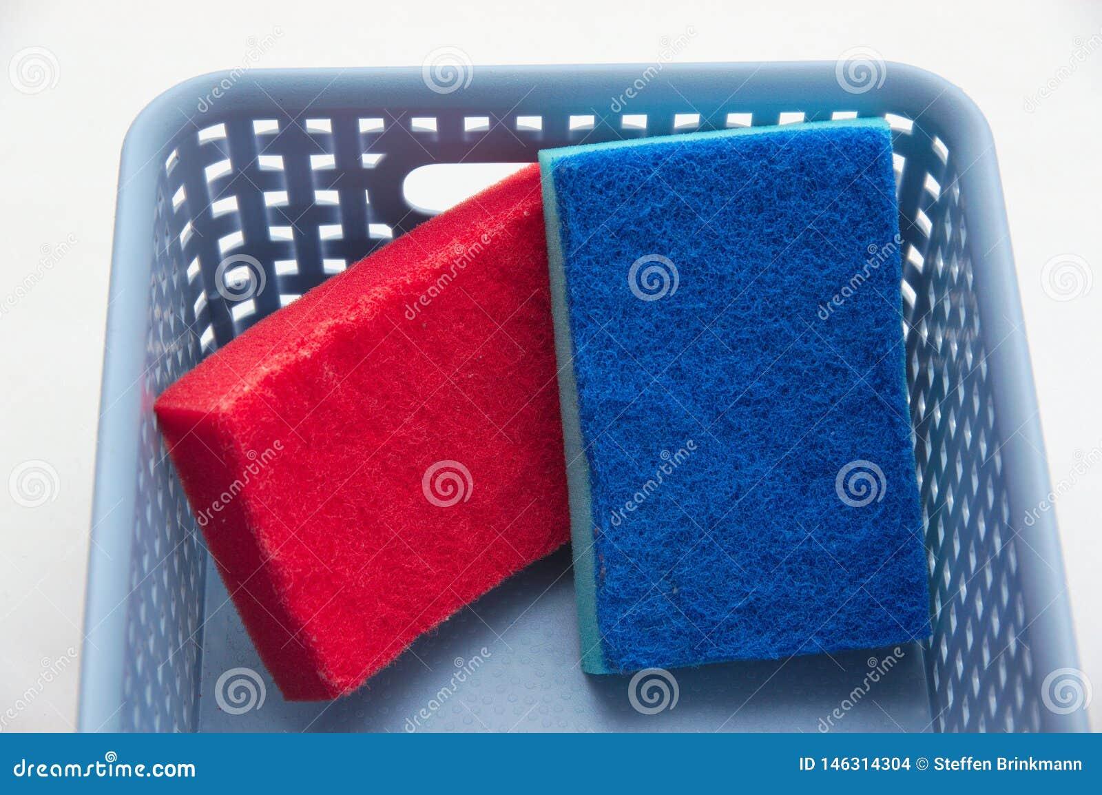 Un rosso e una spugna blu in un canestro di plastica