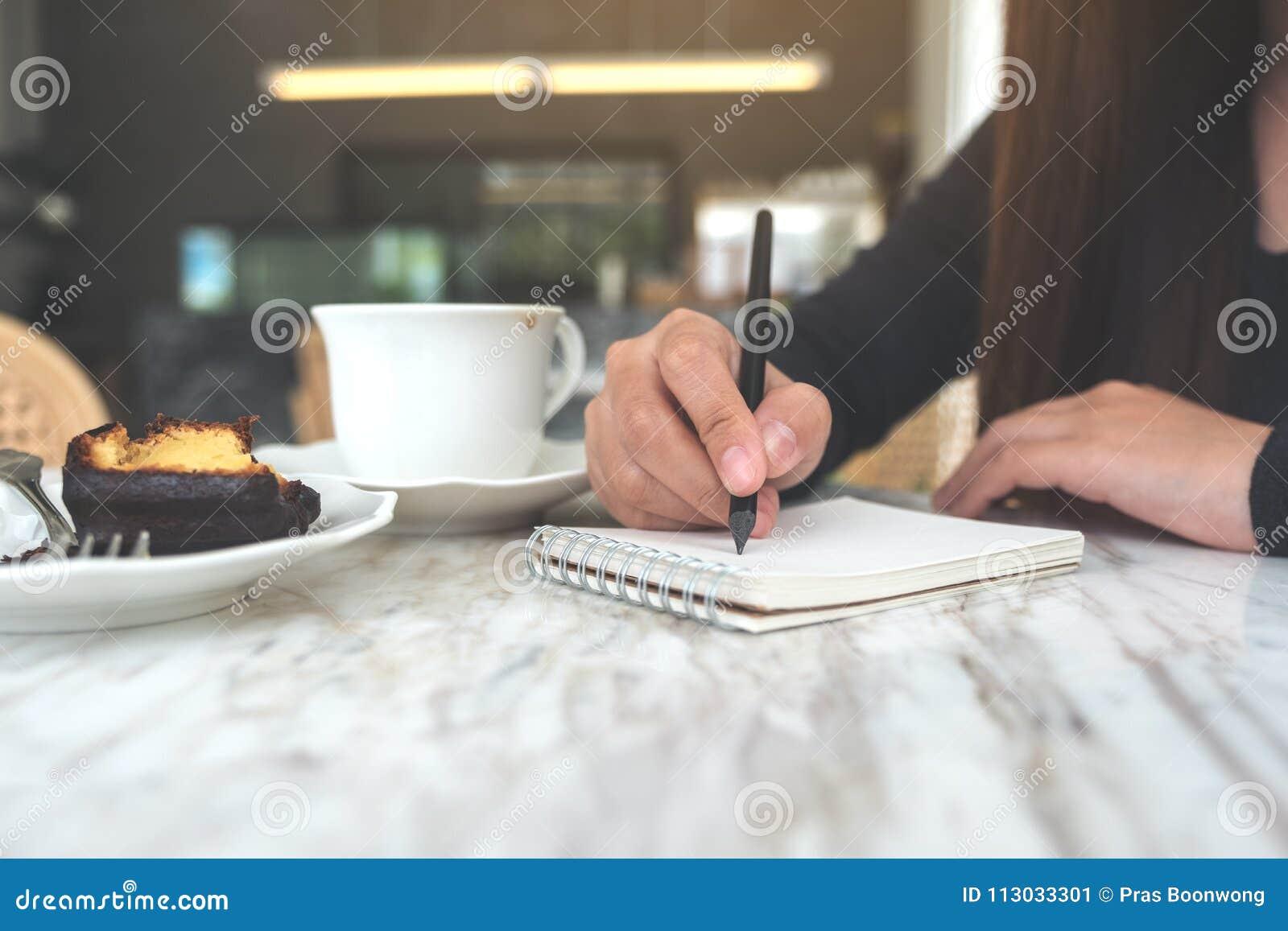 Un ` s de la mujer da anotar en un cuaderno en blanco blanco con la taza y el postre de café en la tabla en café