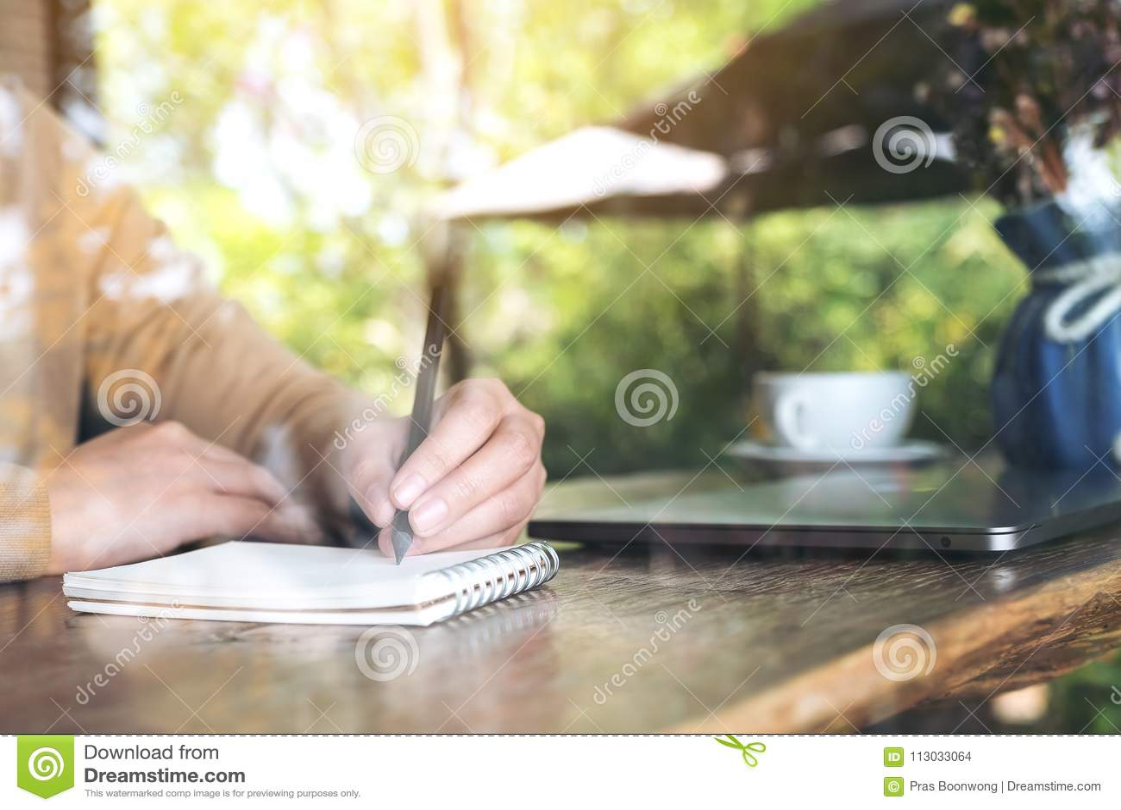 Un ` s de la mujer da la escritura en un cuaderno en blanco con el ordenador portátil en la tabla de madera