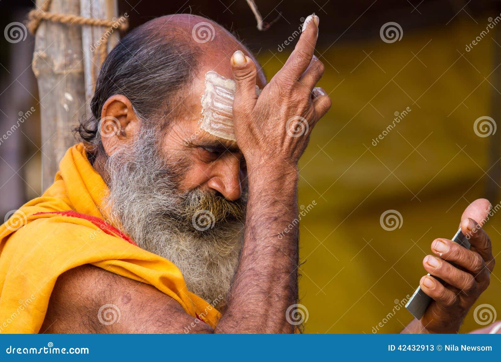 Un sacerdote hindú que aplica marcas de la frente en el Kumbha Mela en la India