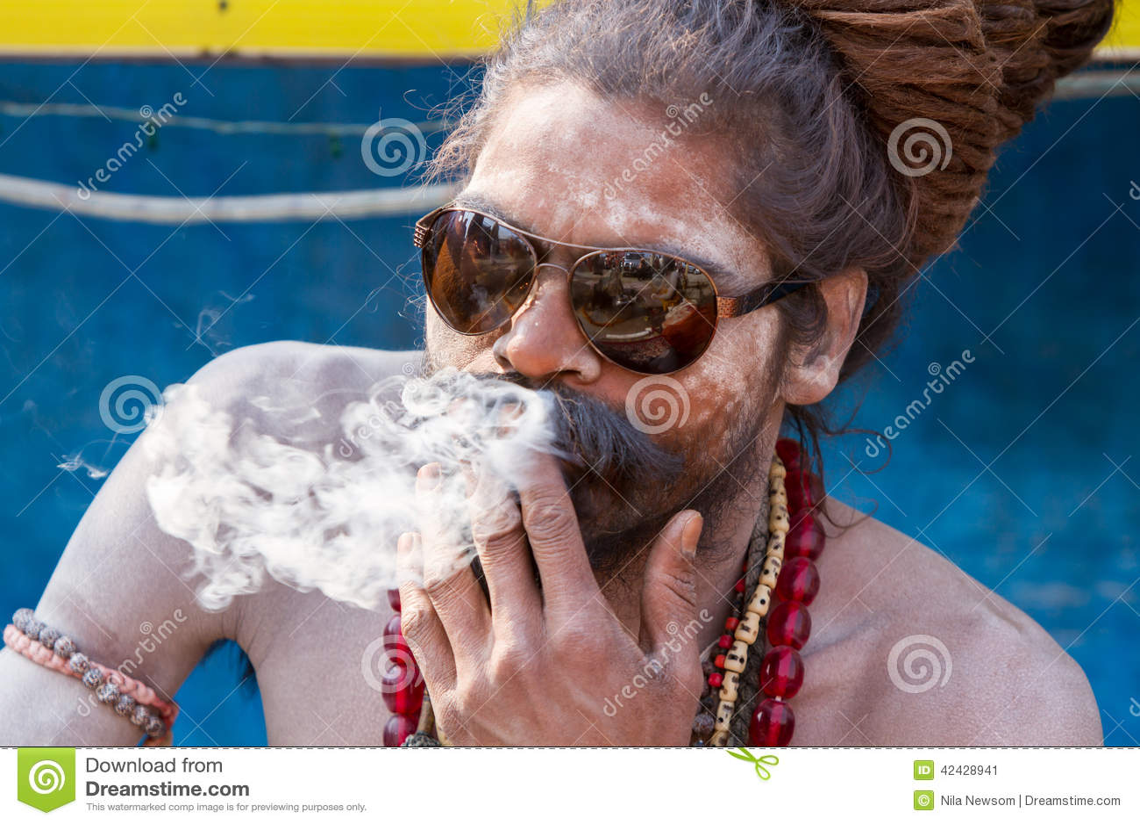 Un sadhu hindú que fuma un cigarrillo - la India