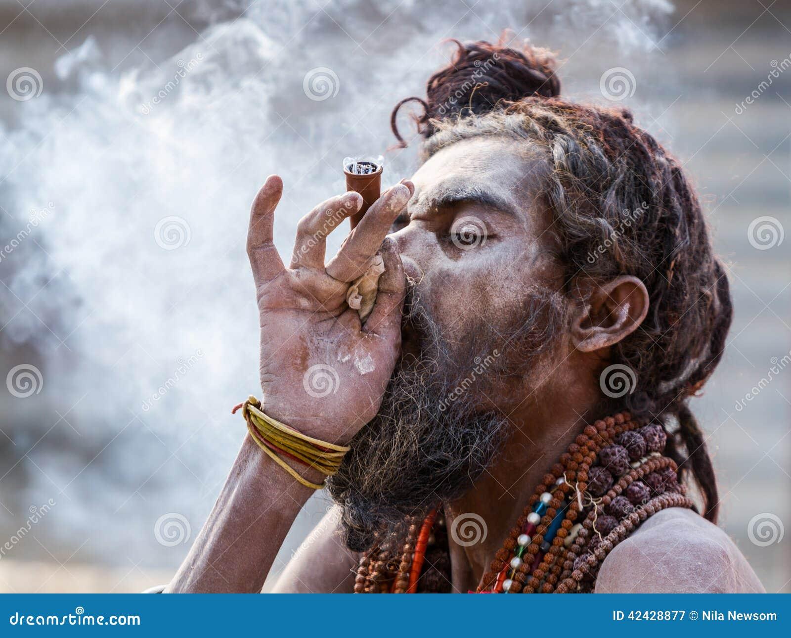 Un sadhu hindú que fuma un tubo de hachís - la India