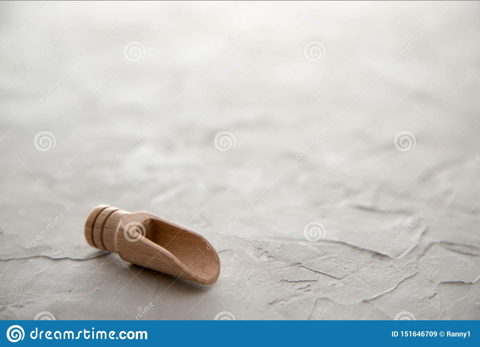 Un scoop en bois vide pour des épices se trouve sur un fond concret Place pour le texte