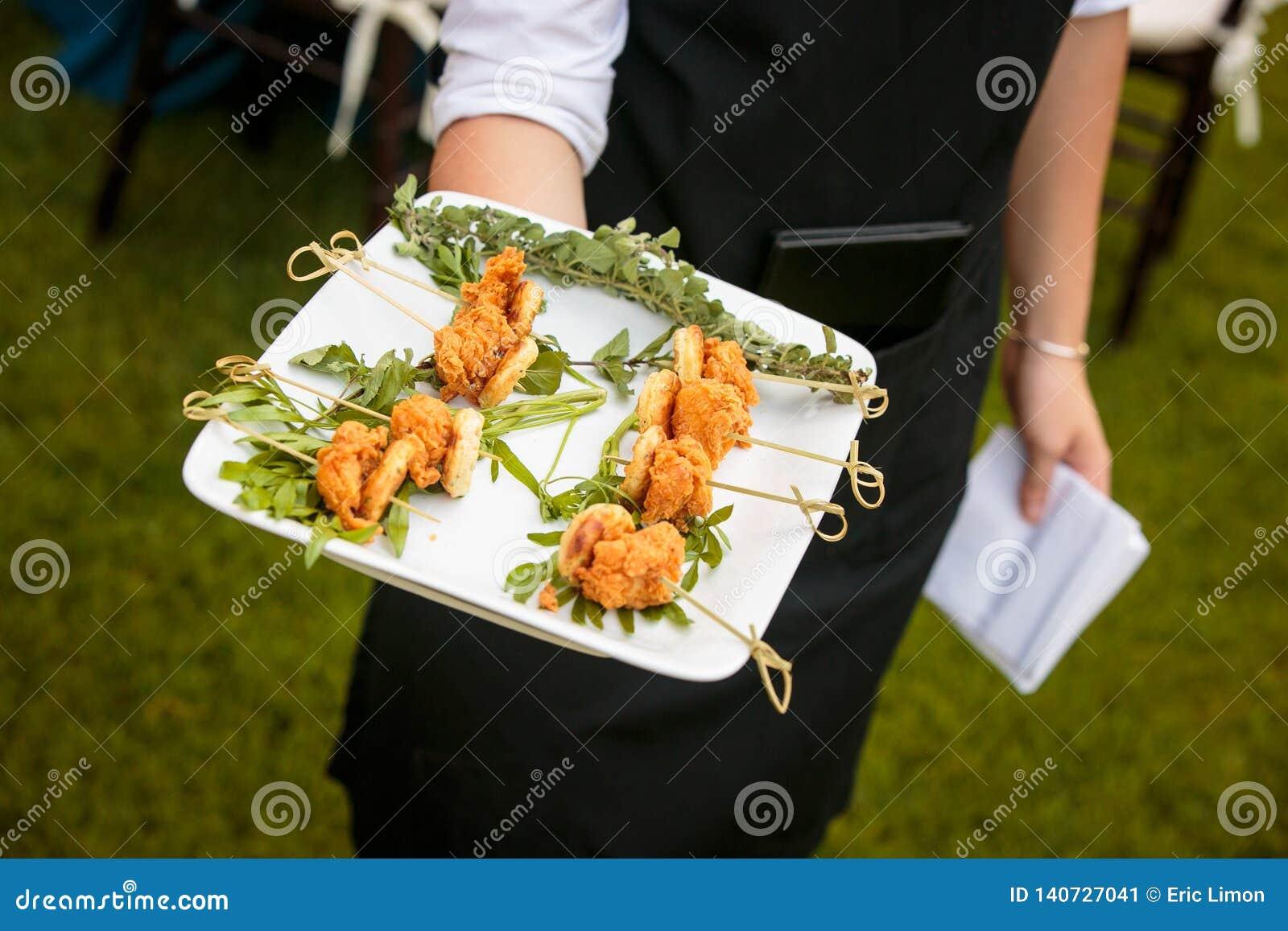 Un serveur tenant un plat de mini poulet frit et gaufres - épouser la série de restauration