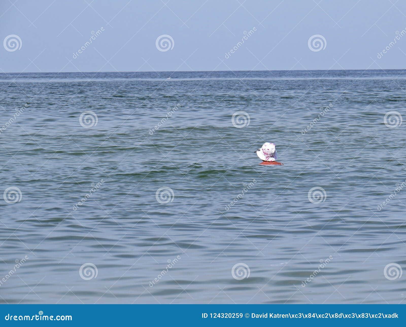 Un singolo nuoto di signora Alone Silhouette Head della donna nel mare ondeggia con il cappello bianco