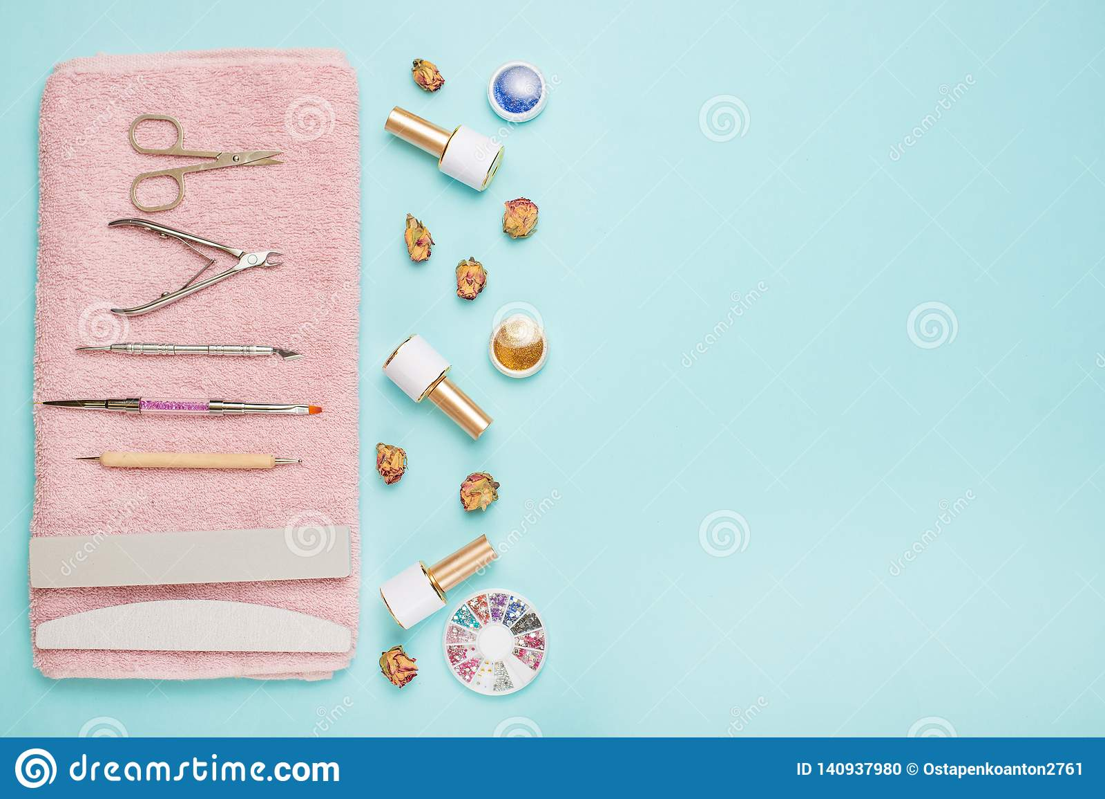 Un sistema de las herramientas cosméticas para la manicura y la pedicura en un fondo azul Pulimentos del gel, ficheros de clavo y