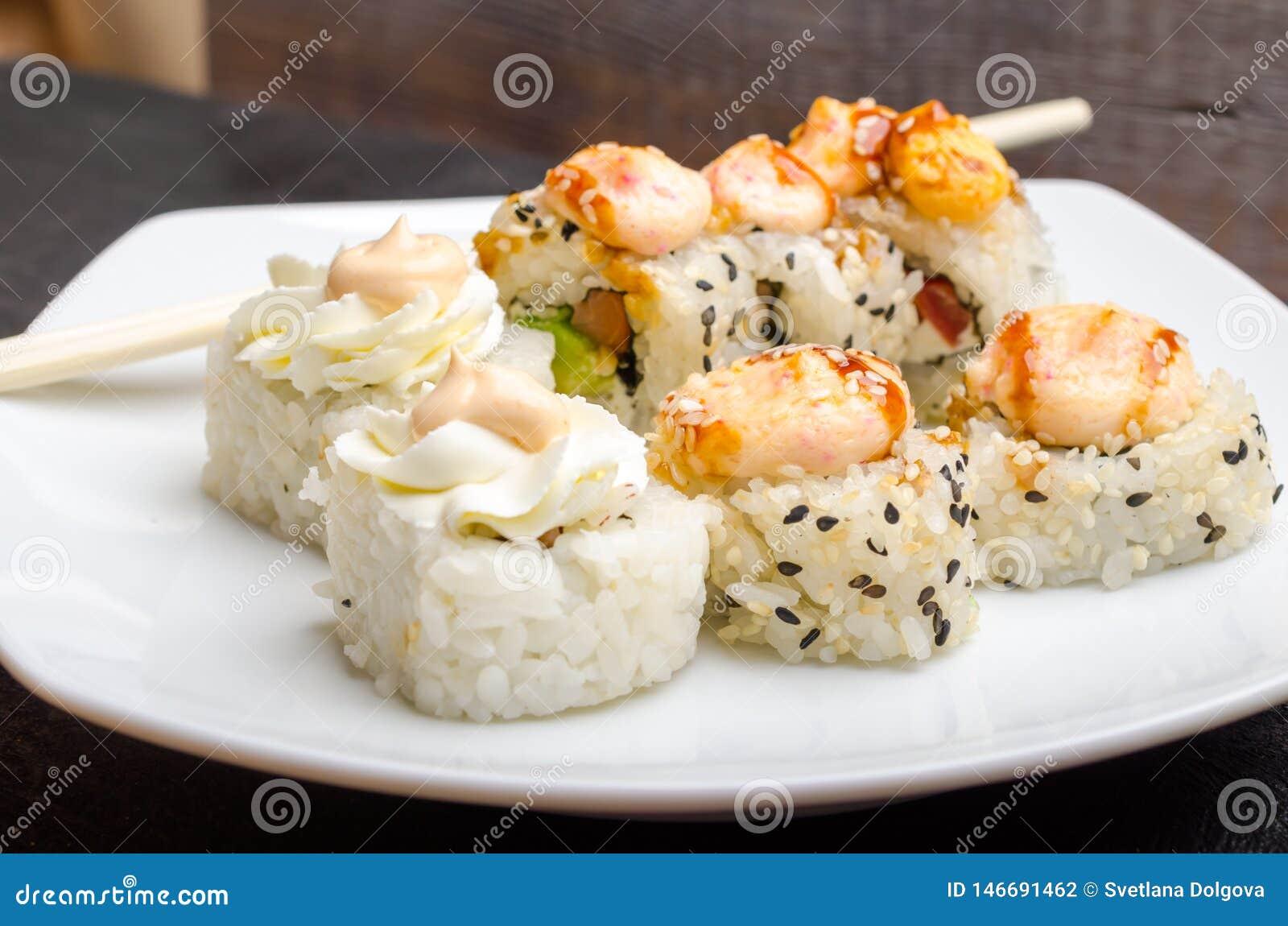 Un sistema de rollos de sushi japoneses cortados en un primer blanco de la placa