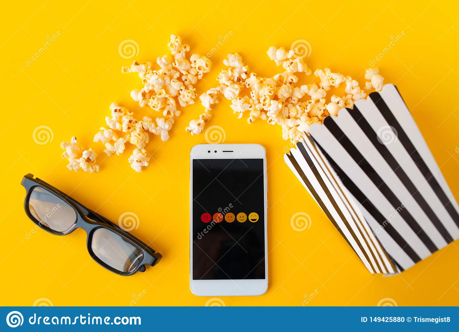Un smartphone blanco con los smilies en la pantalla, los vidrios 3d, una caja de papel rayada blanco y negro y las palomitas disp