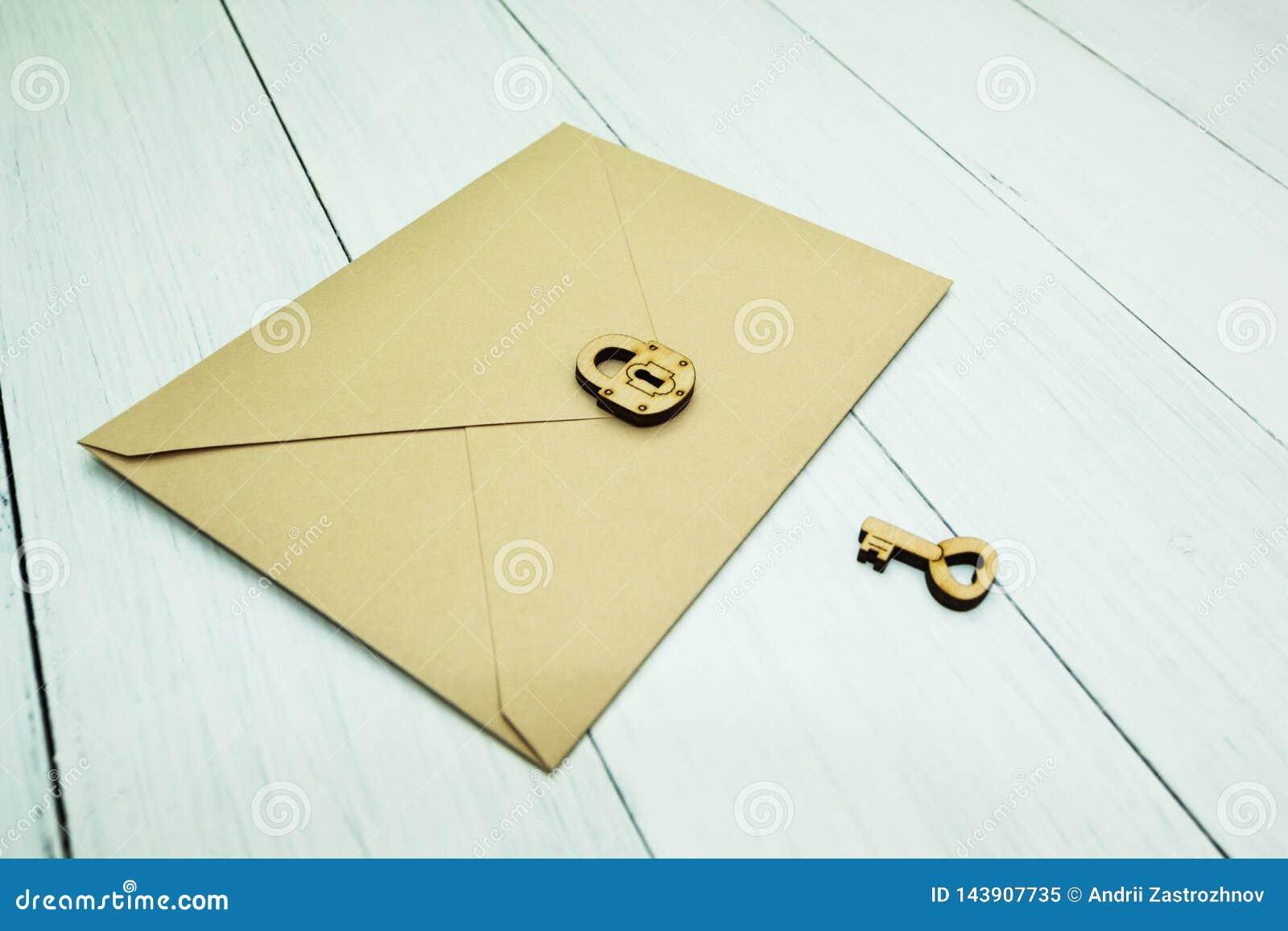 Un sobre de papel del correo es cerrado con una cerradura al lado de la llave en una tabla blanca, un secreto