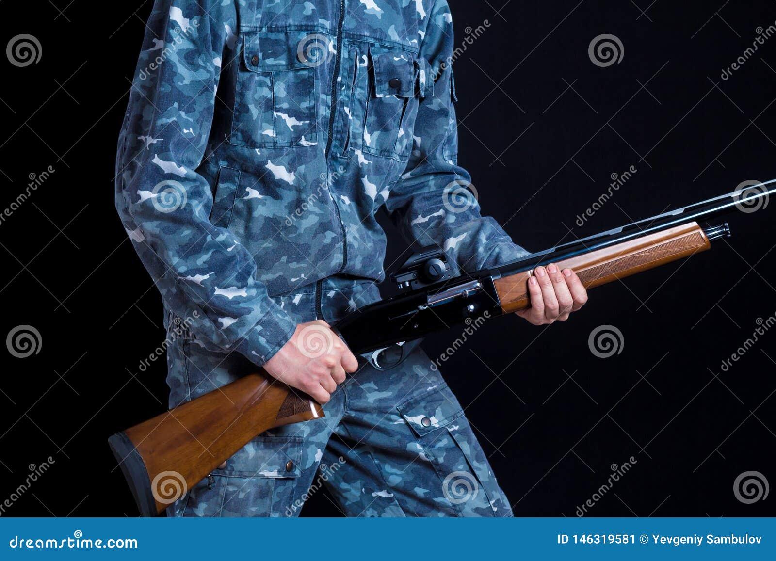 Un soldado en uniforme militar con una escopeta Juegos de guerra Preparación para la primavera, caza del otoño Soldado o cazador