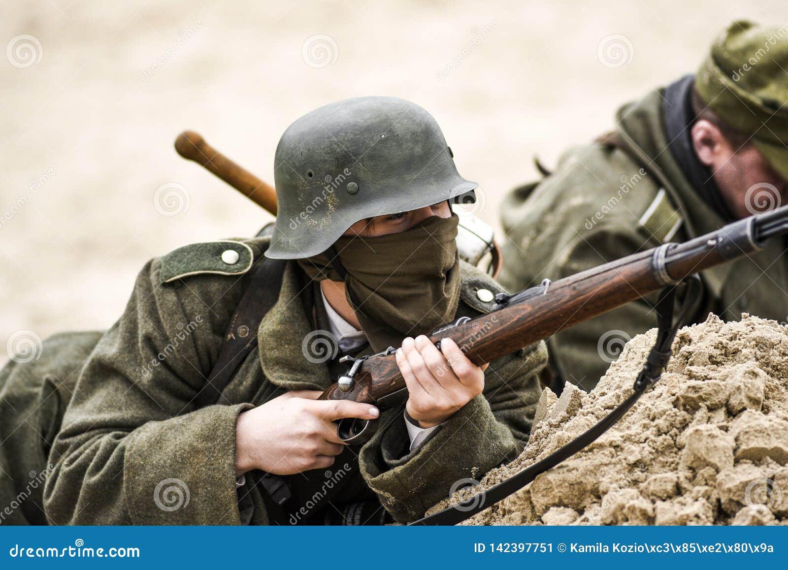 Un soldat allemand dans un fossé avec un fusil dans sa main Reconstitution historique de la bataille
