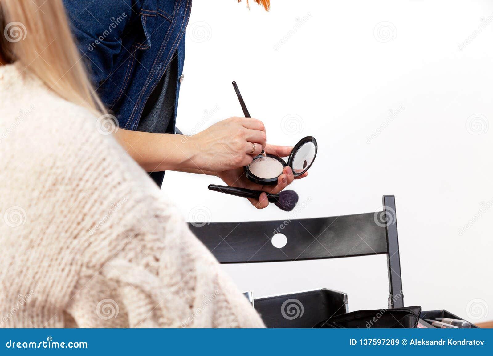 Un styliste au travail dans un studio de maquillage sélectionne un produit cosmétique d une palette avec un plan rapproché de bro