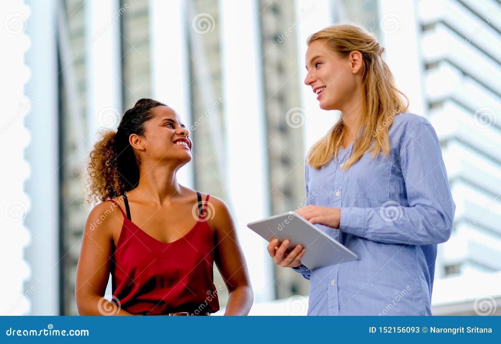Un support de fille de métis et discuter avec la fille caucasienne blanche qui tient le comprimé