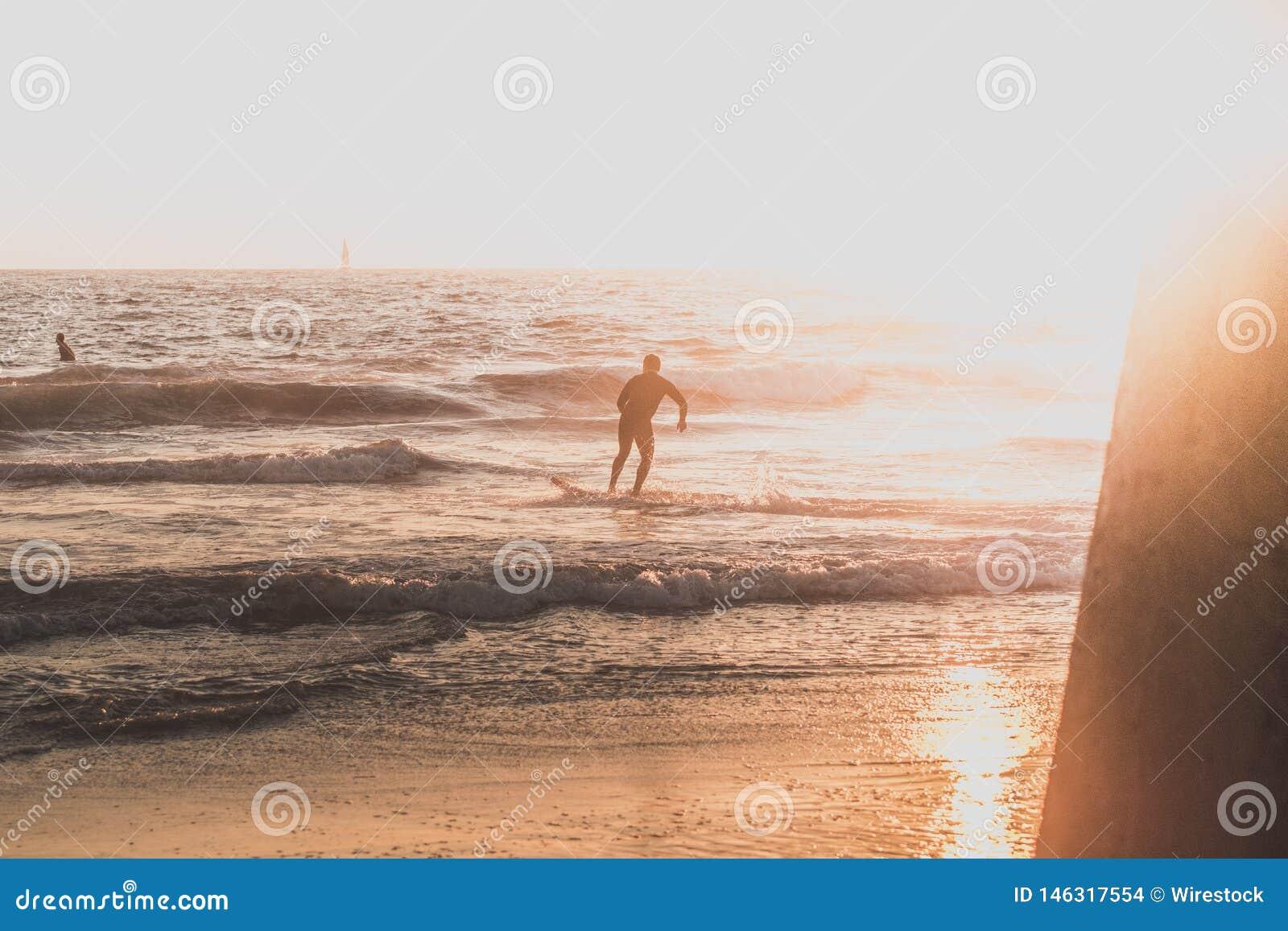 Un surfer courant sur la plage