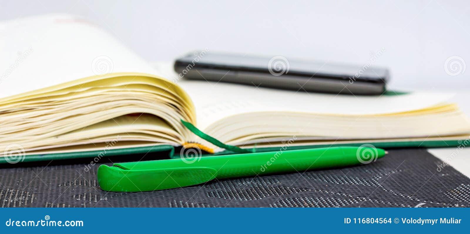 Un taccuino aperto con la penna e telefono per la registrazione importante dentro