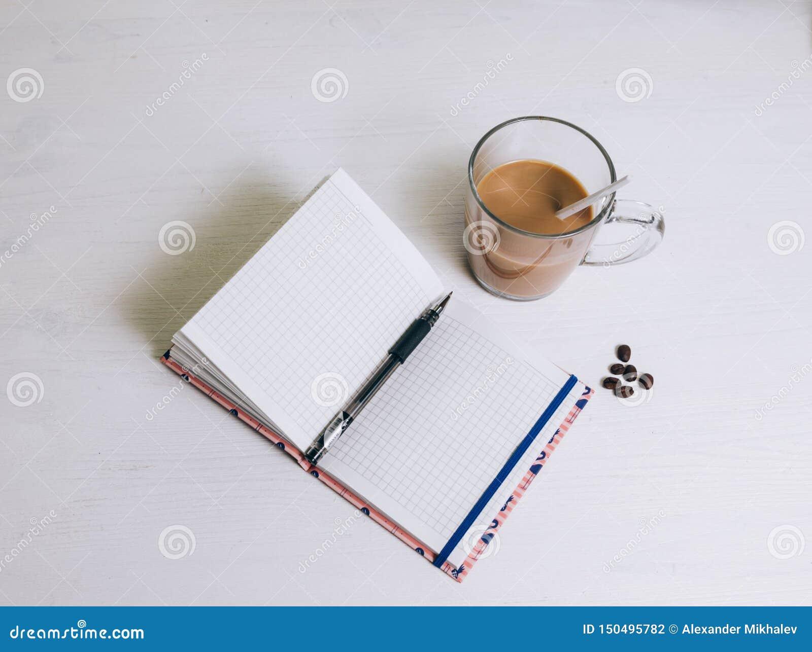 Un taccuino sulla tavola accanto a vetro di caffè