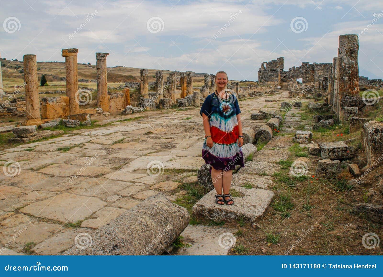 Un teatro griego antiguo clásico en Pamukkale, Denizli, Turquía y una mujer joven blanca en un vestido del hippie