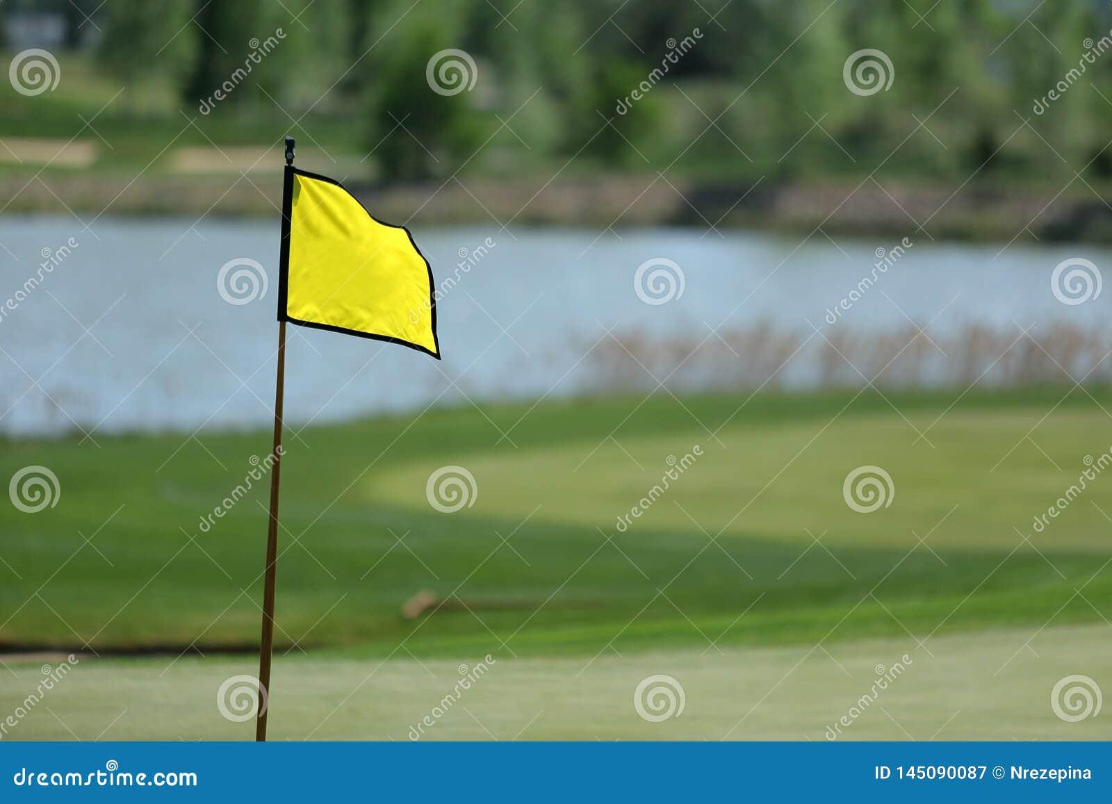 Un terrain de golf avec des routes, des soutes et des étangs et avec le drapeau