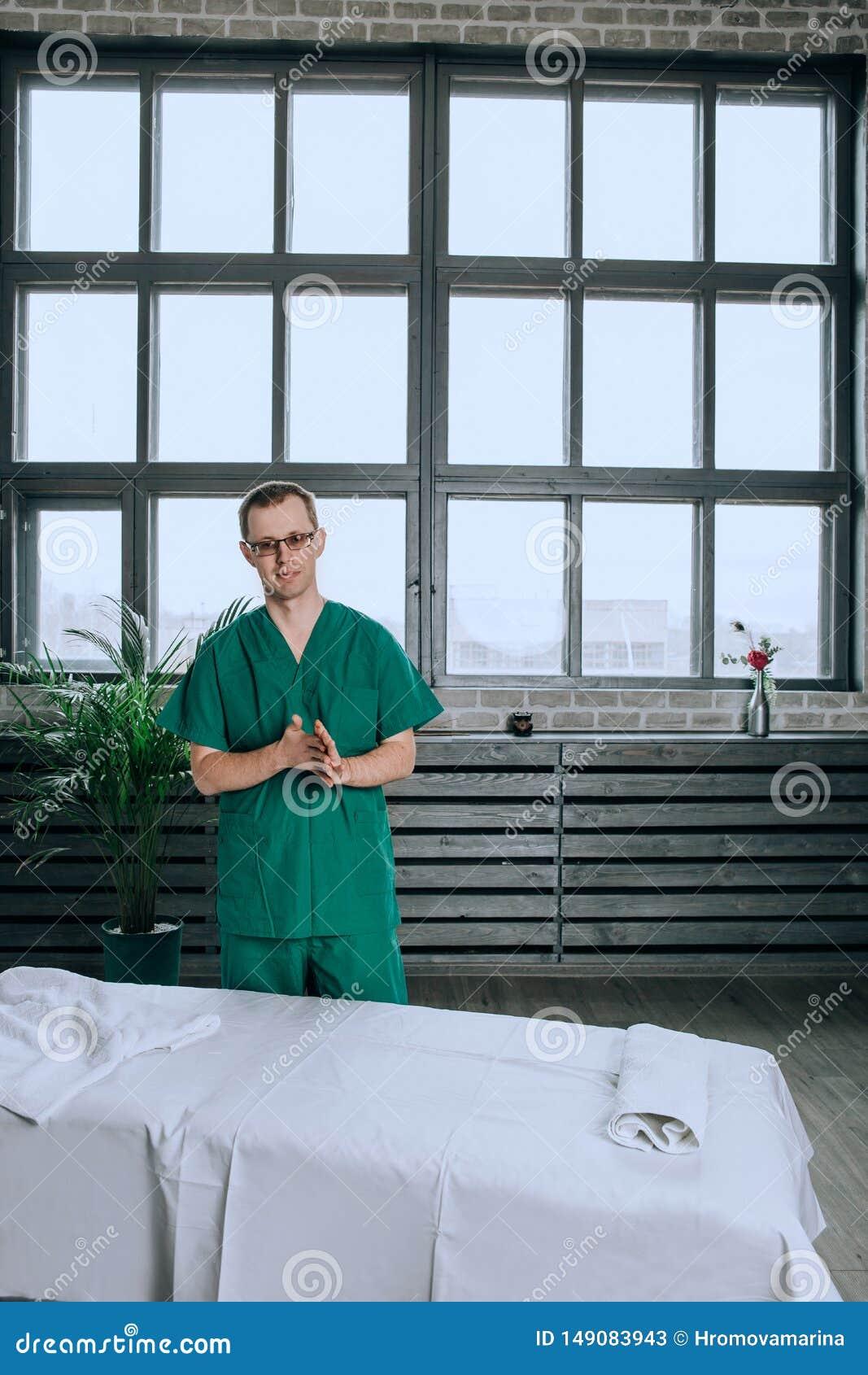 Un thérapeute masculin de massage dans un costume vert est souriant et étant prêt pour le travail