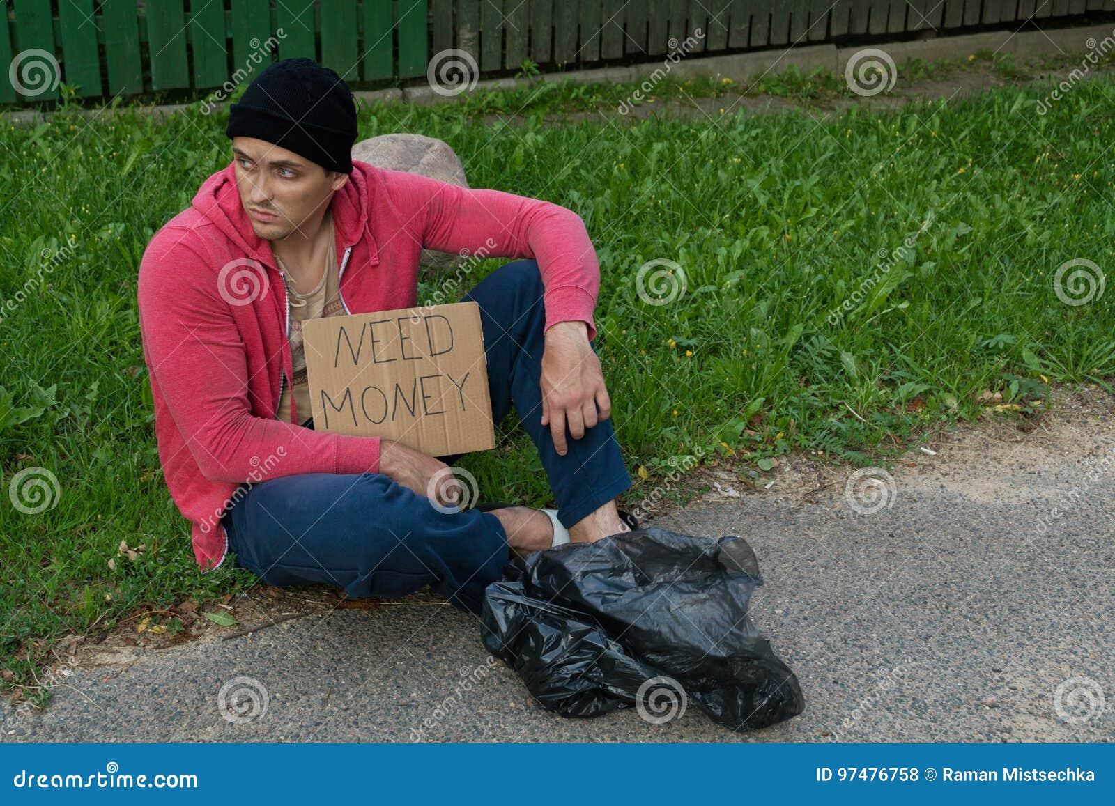 Un tipo senza tetto si siede sul marciapiede con un cartone e un iscrizione: soldi di bisogno