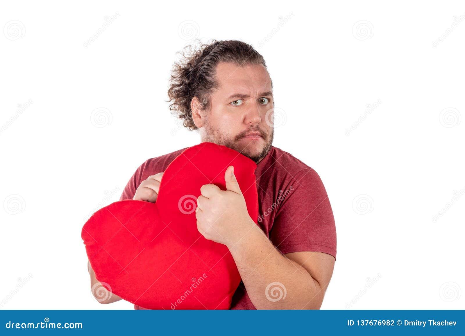 Un tir de studio d un gros homme jugeant un oreiller en forme de coeur rouge d isolement sur le fond blanc