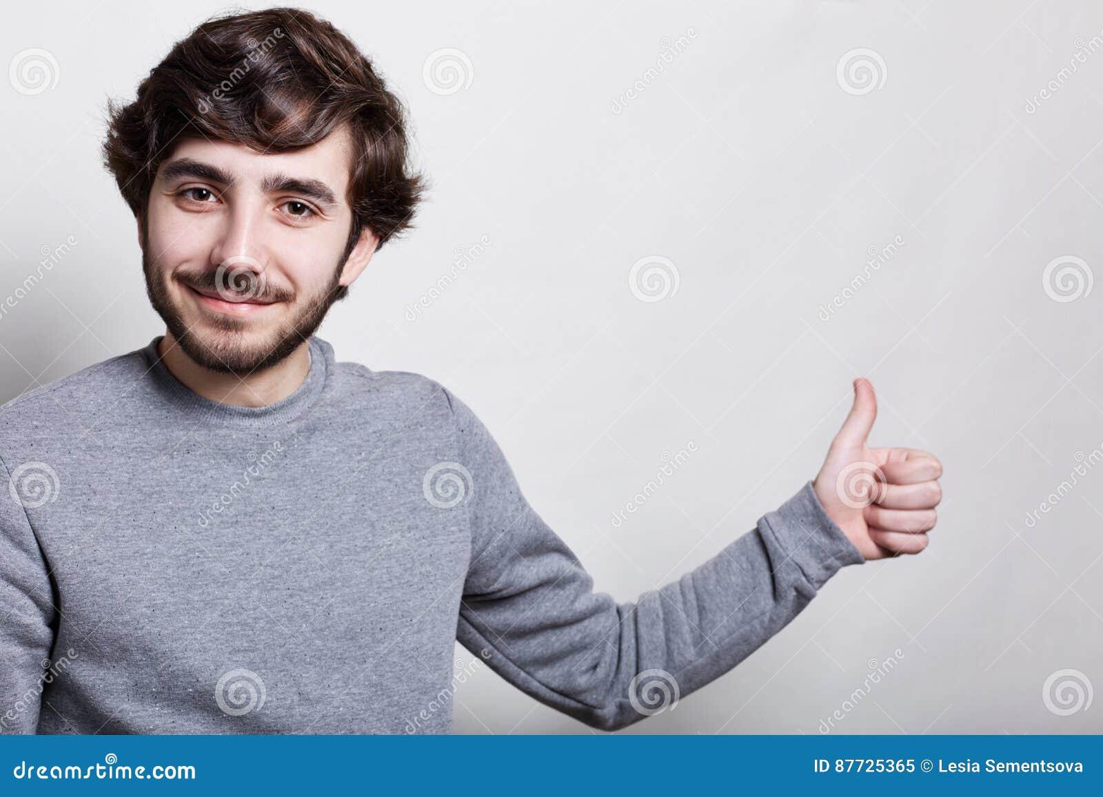 Un tiro del estudio del hombre elegante con el peinado y la barba de moda grandes de los ojos oscuros de las cejas gruesas se vis