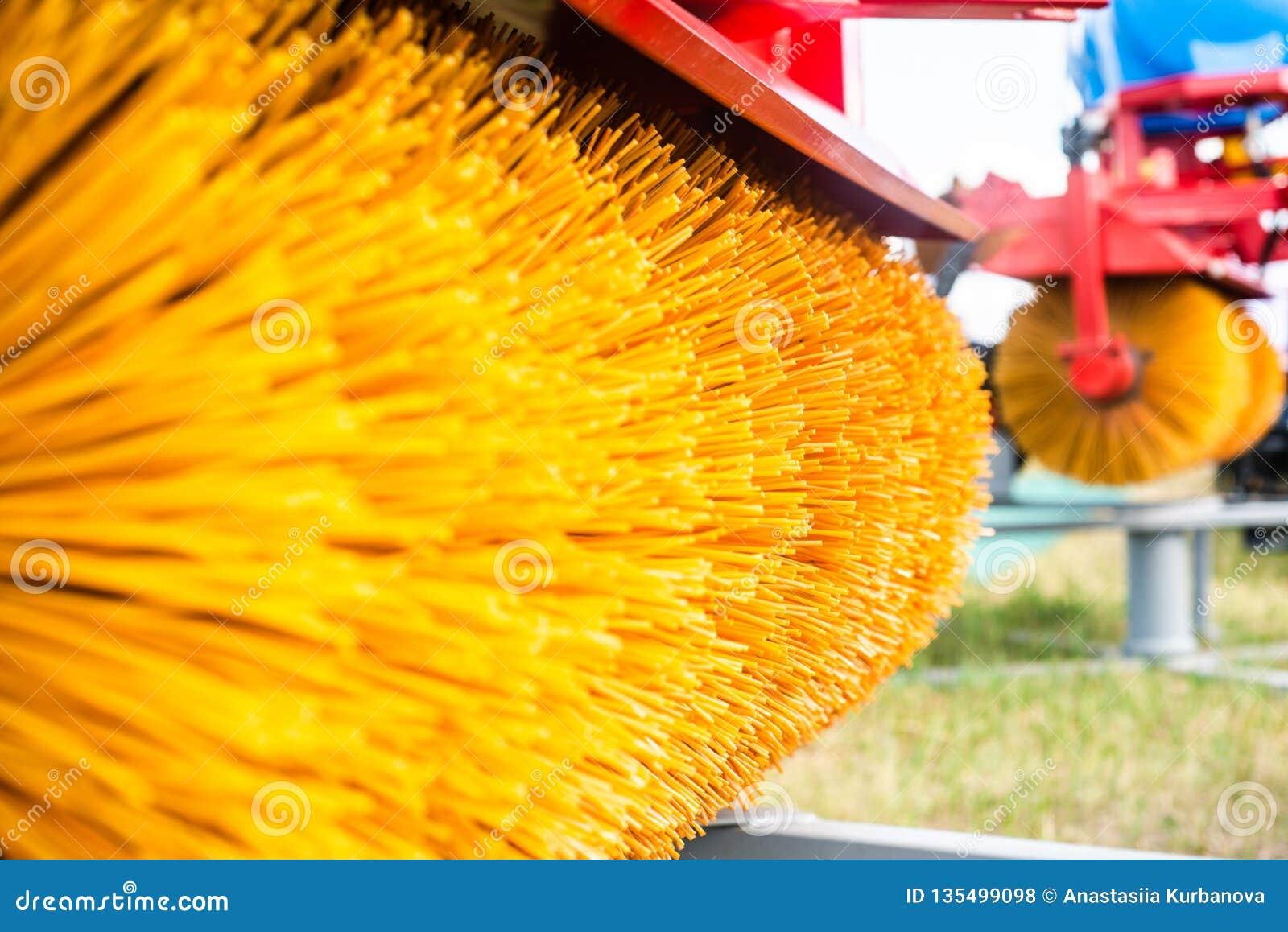 Un toldo en un tractor con un cepillo giratorio despeja la nieve de los caminos, pila amarilla