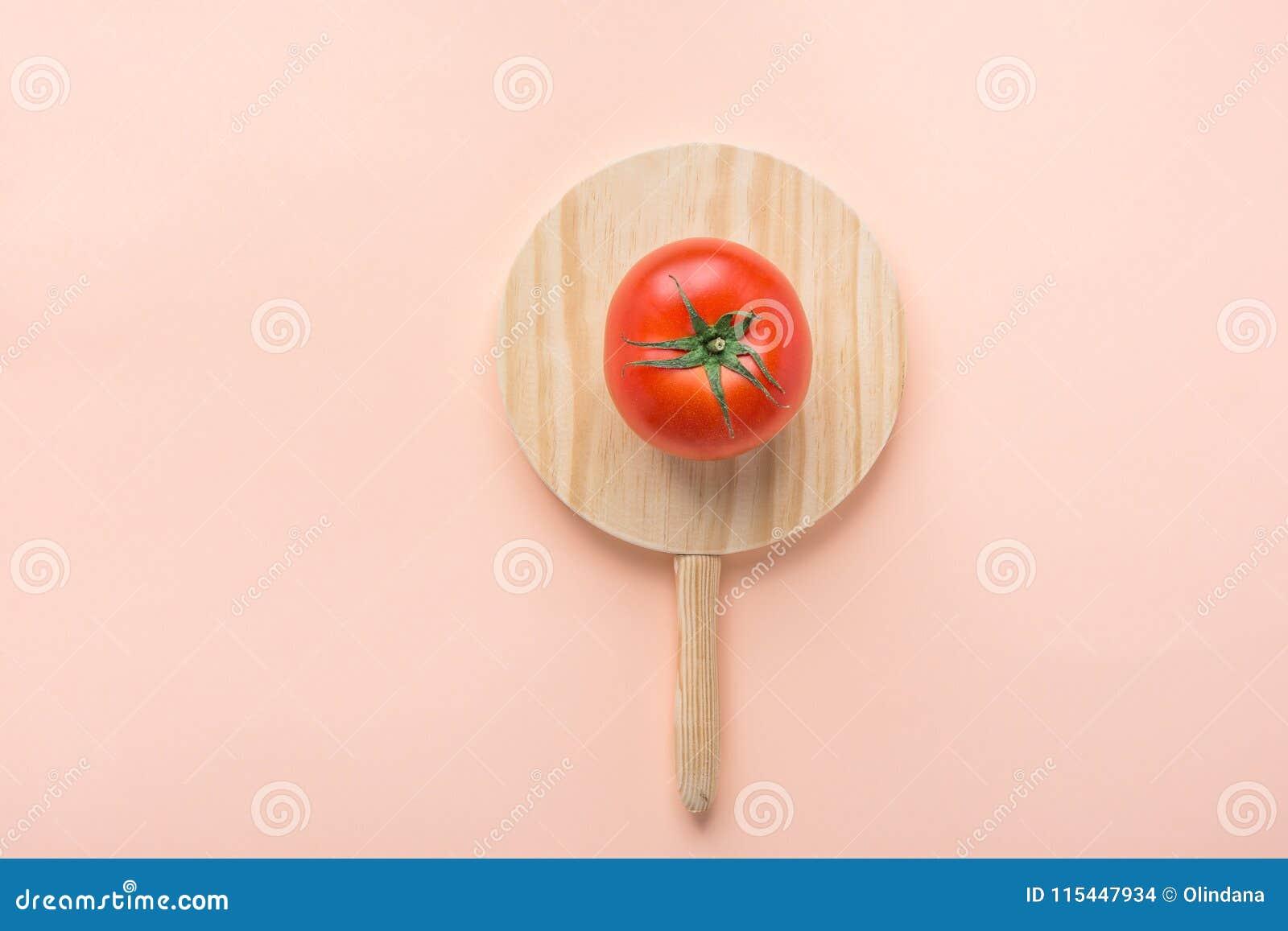 Un tomate orgánico maduro con las hojas del verde en tabla de cortar de madera redonda en fondo rosado Flámula de la bandera del