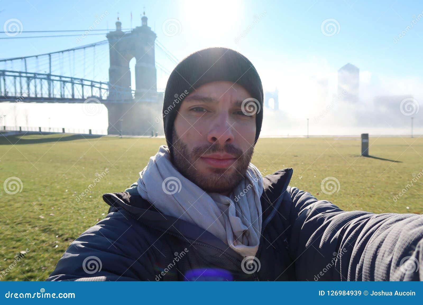 Un touriste prend un selfie devant un beau pont