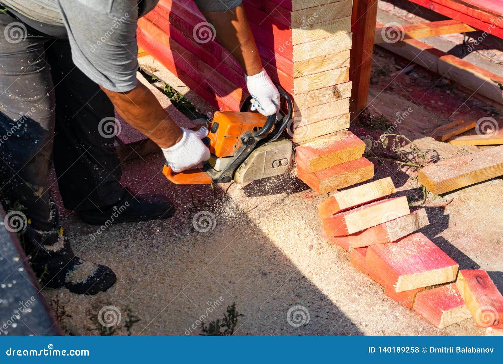 Un trabajador asierra de un tablero de madera de la motosierra Construcción de la casa