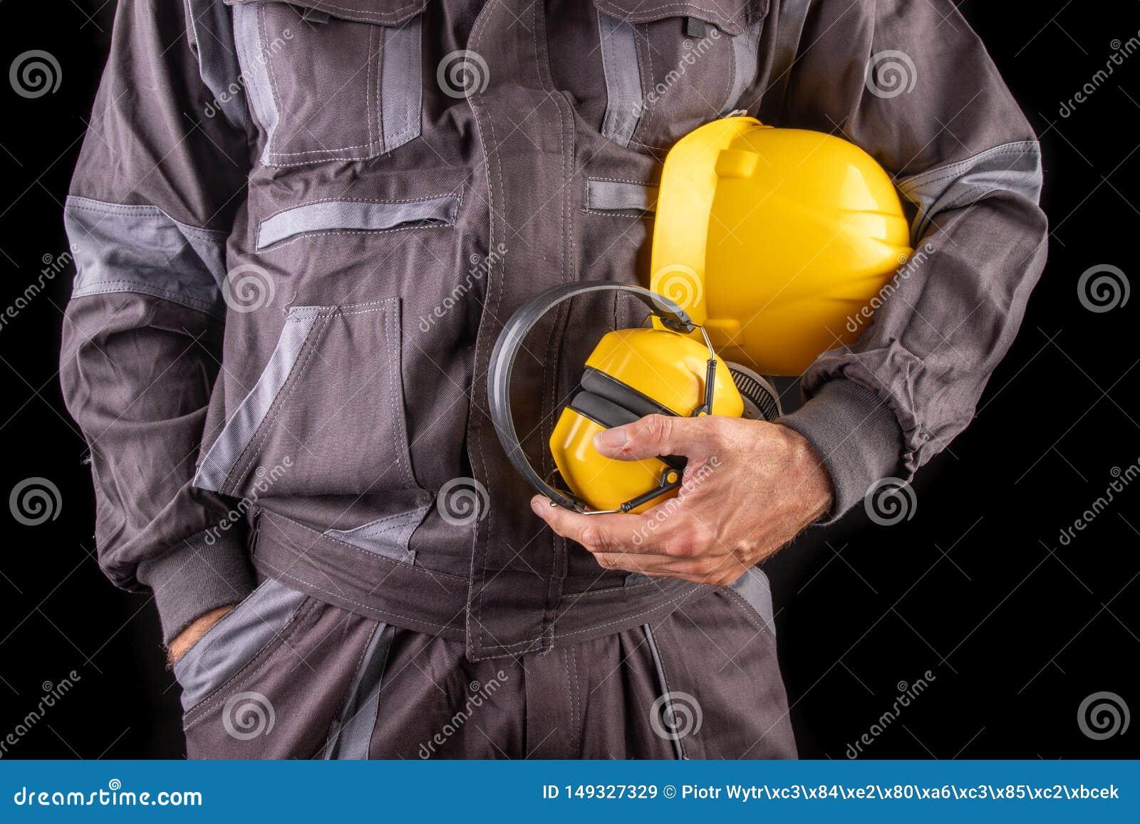 Un trabajador de producci?n en workwear con un casco y los protectores de o?do a disposici?n Workwear especial para los empleados