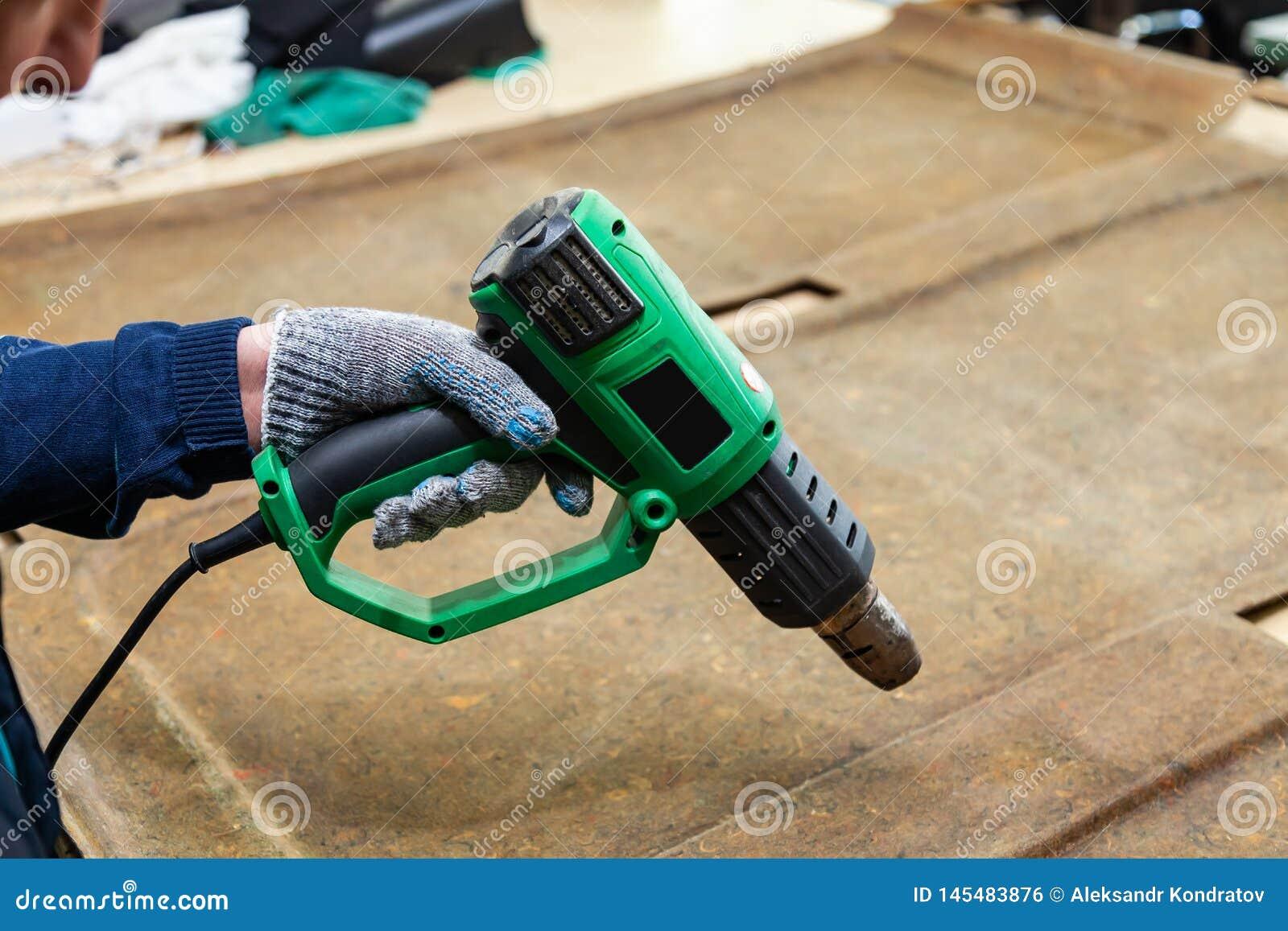 Un trabajador de sexo masculino sostiene en su mano un secador industrial verde vestido en un guante protector y seca el pegament