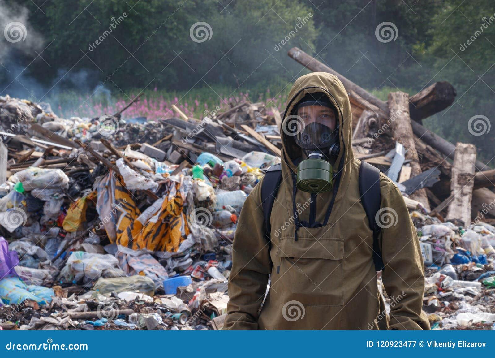 Un trabajador en una careta antigás contra el contexto de la basura ardiente Las muchas bolsas de plástico lanzadas a la descarga