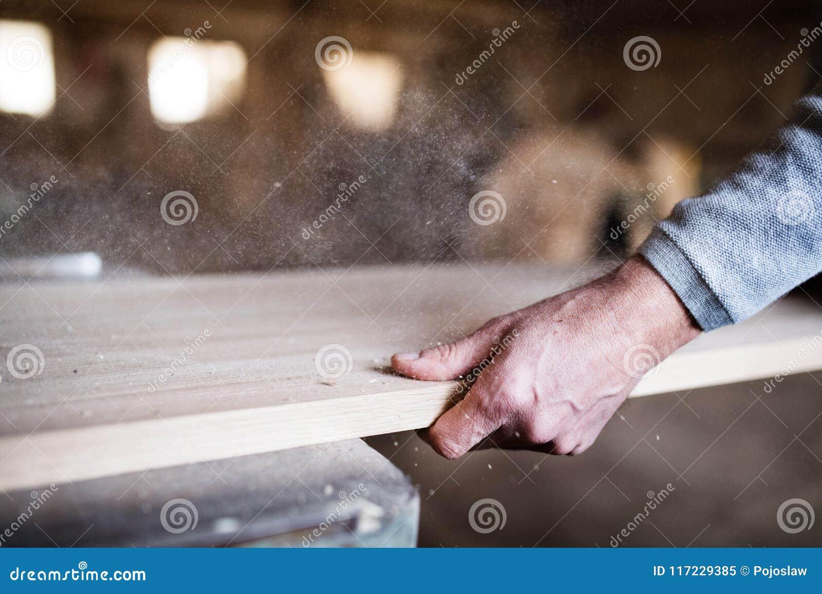 Un trabajador irreconocible del hombre en el taller de la carpintería, trabajando con madera