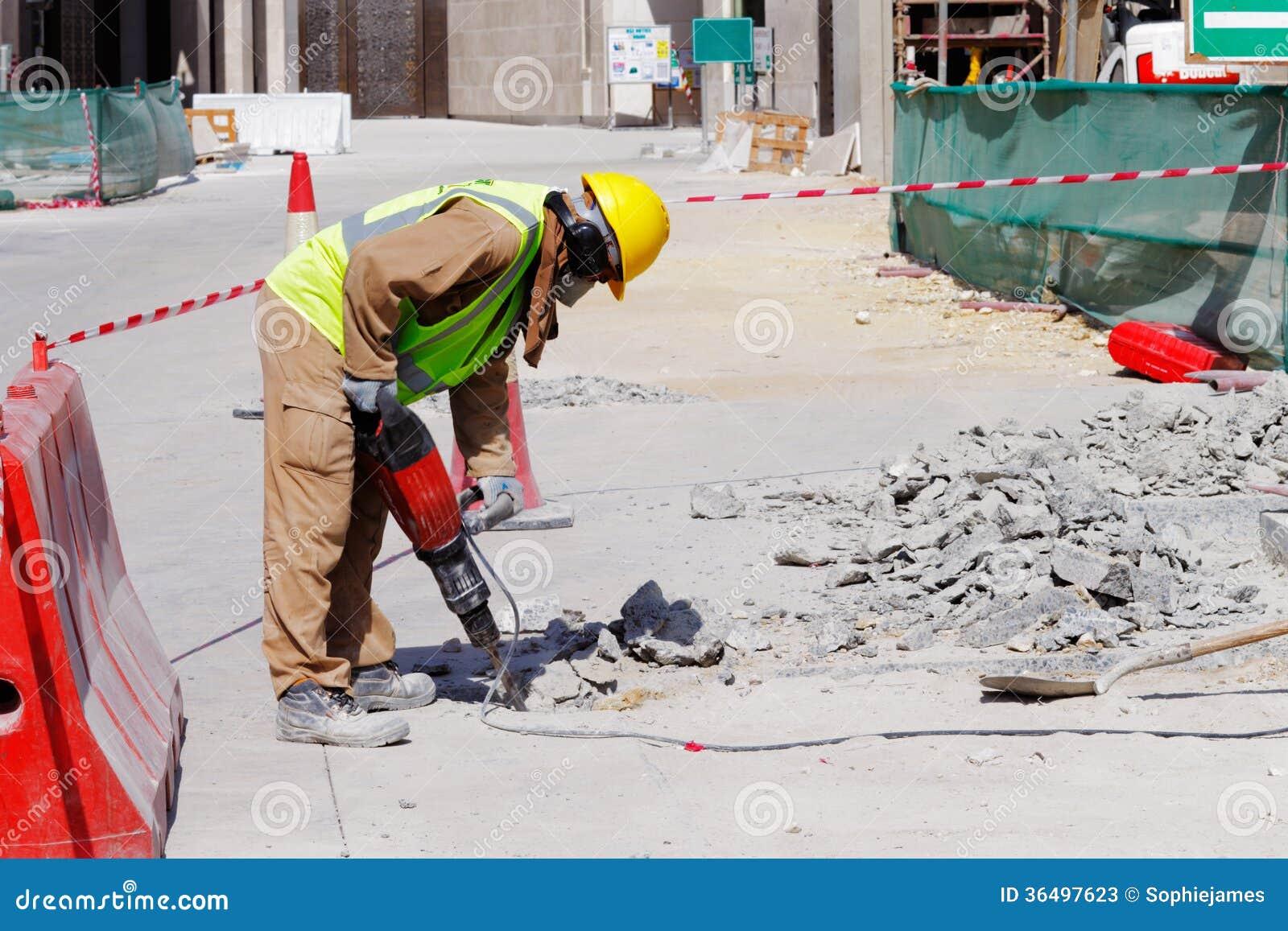 Un trabajador utiliza un martillo perforador para romper for Pavimento de cemento