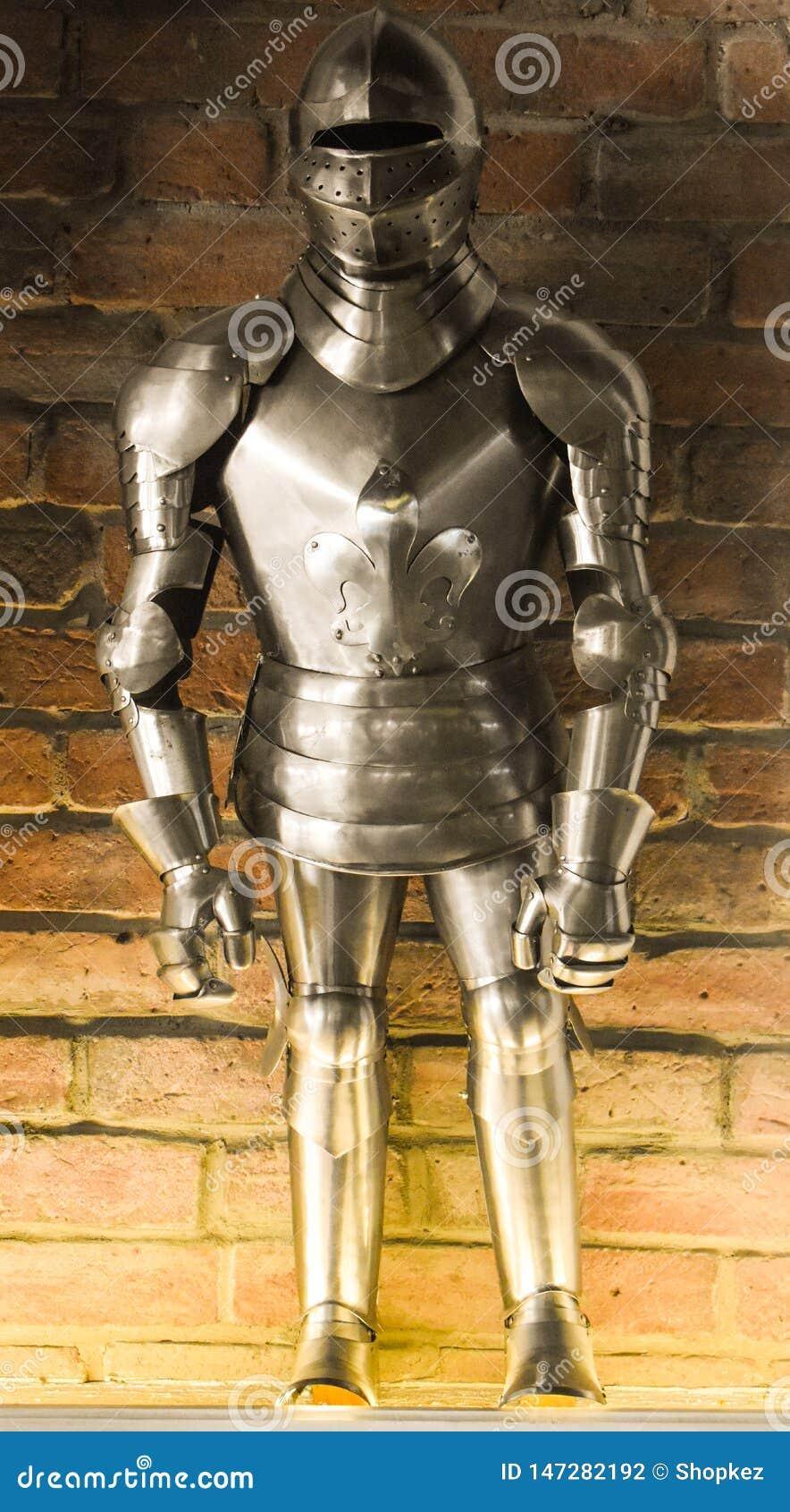 Un traje lleno europeo de la armadura del vintage contra el fondo de la pared de ladrillo