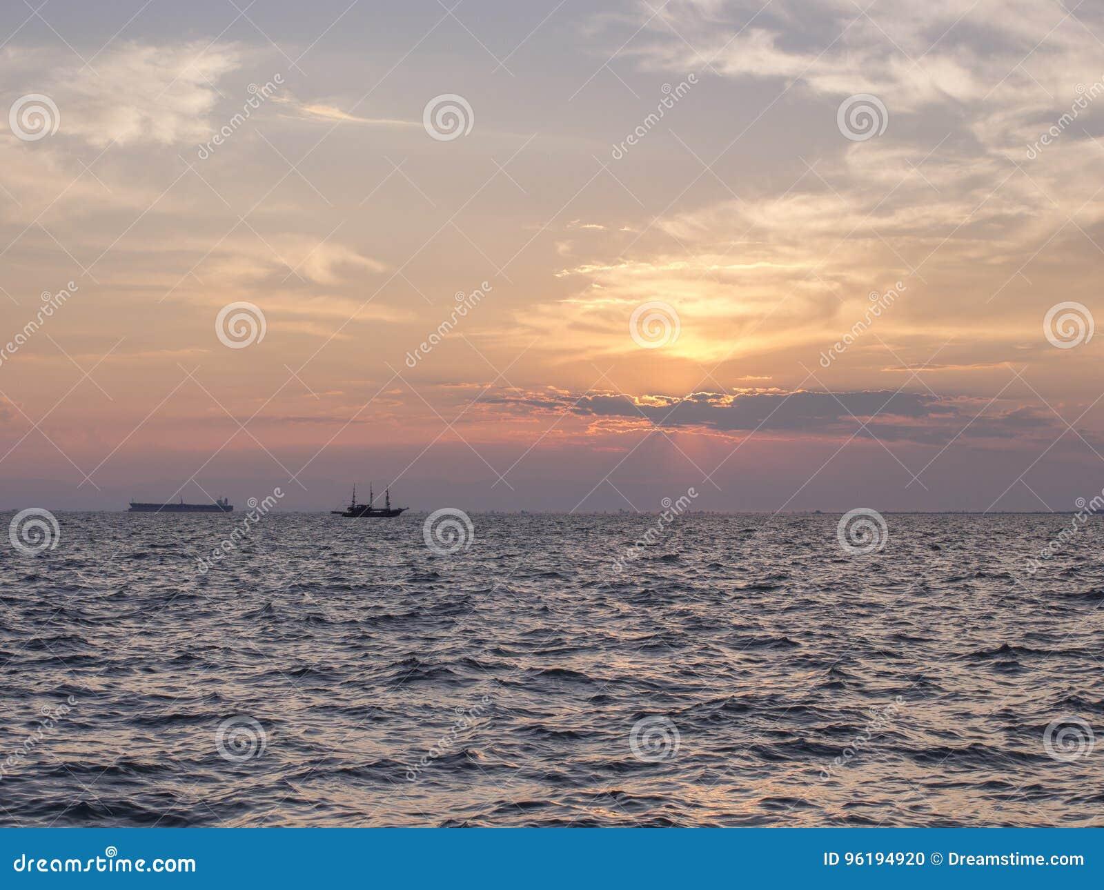 Un tramonto sopra il mare con due siluette delle navi