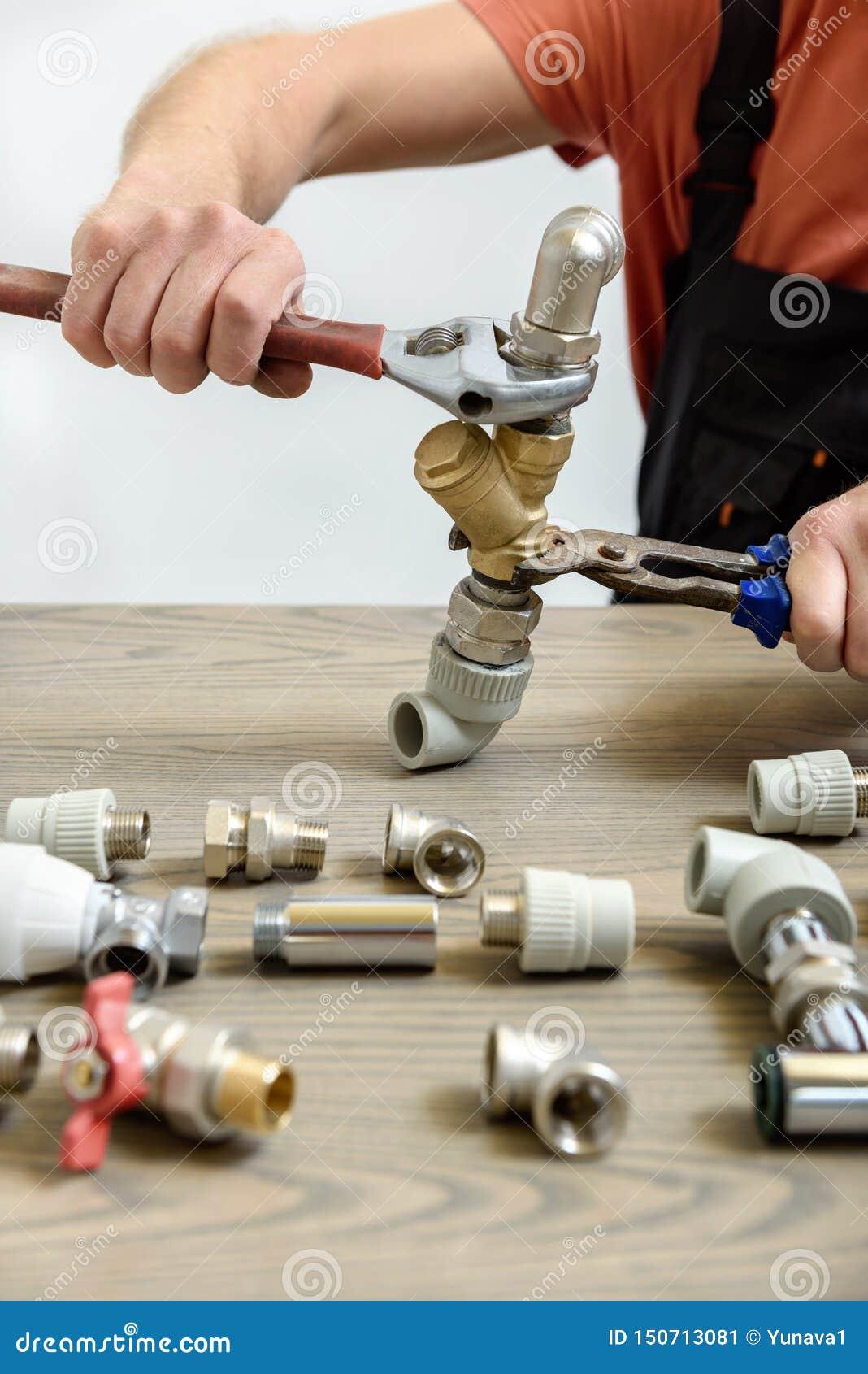 Un travailleur relie des éléments de la tuyauterie