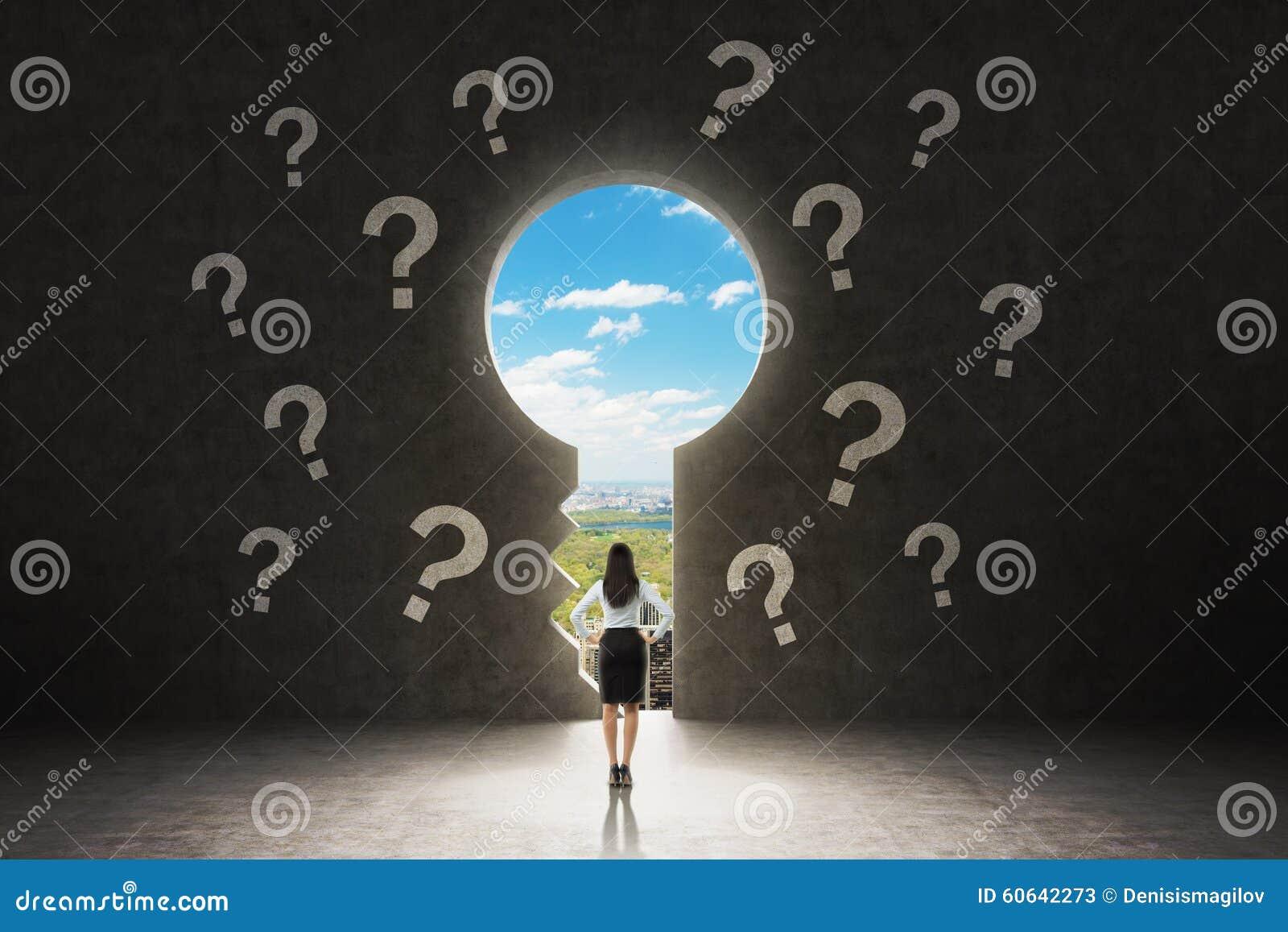 Un trou de la serrure dans le mur en béton Une dame d affaires habillée dans le costume formel regarde New York City dans le trou