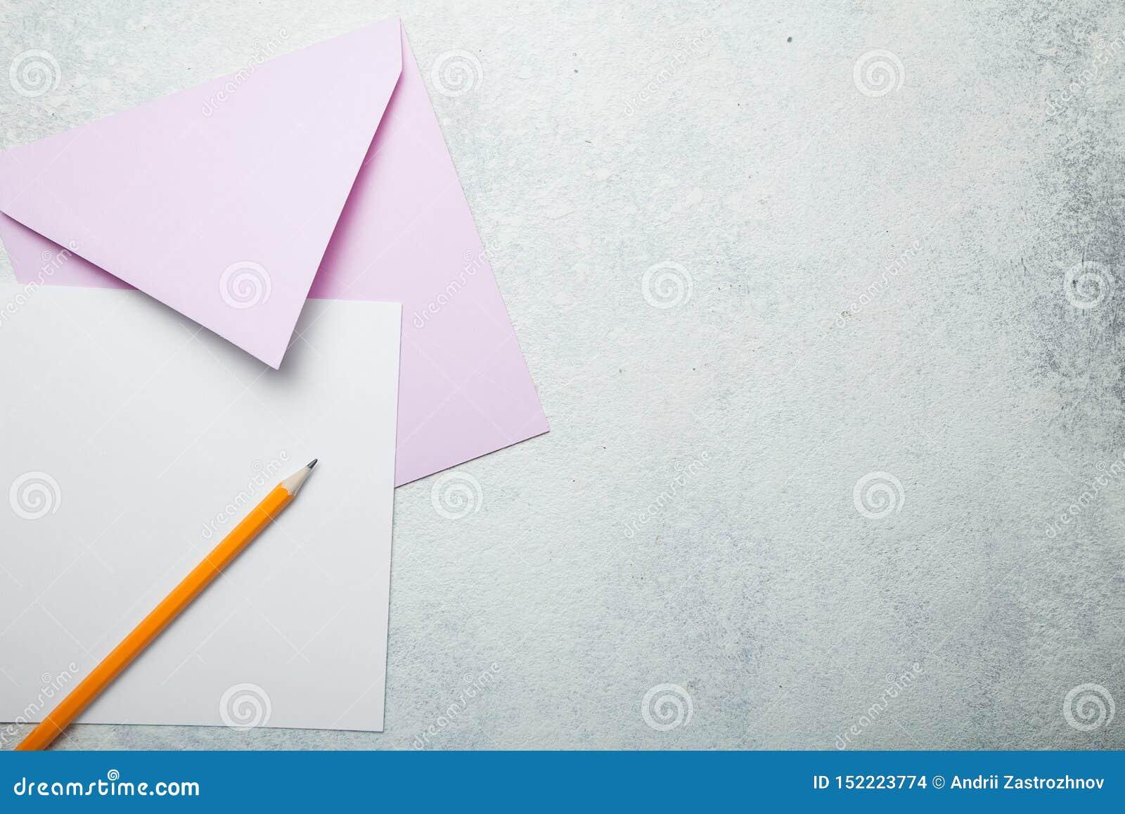 Un trozo de papel cuadrado vacío con un sobre rosado en un fondo blanco del vintage, una letra de amor al día de tarjeta del día