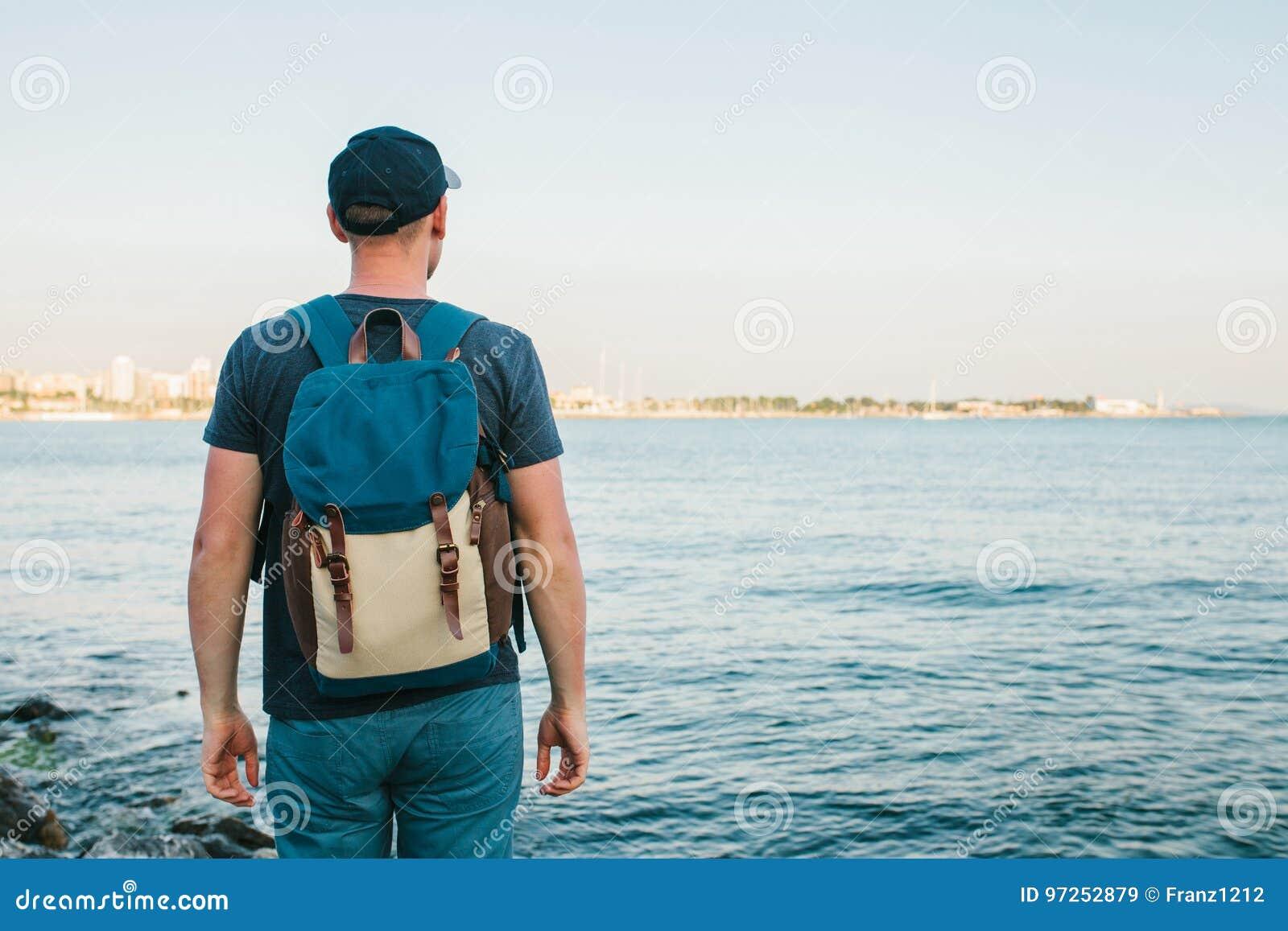 Un turista con una mochila en el viaje de la costa, turismo, reconstrucción