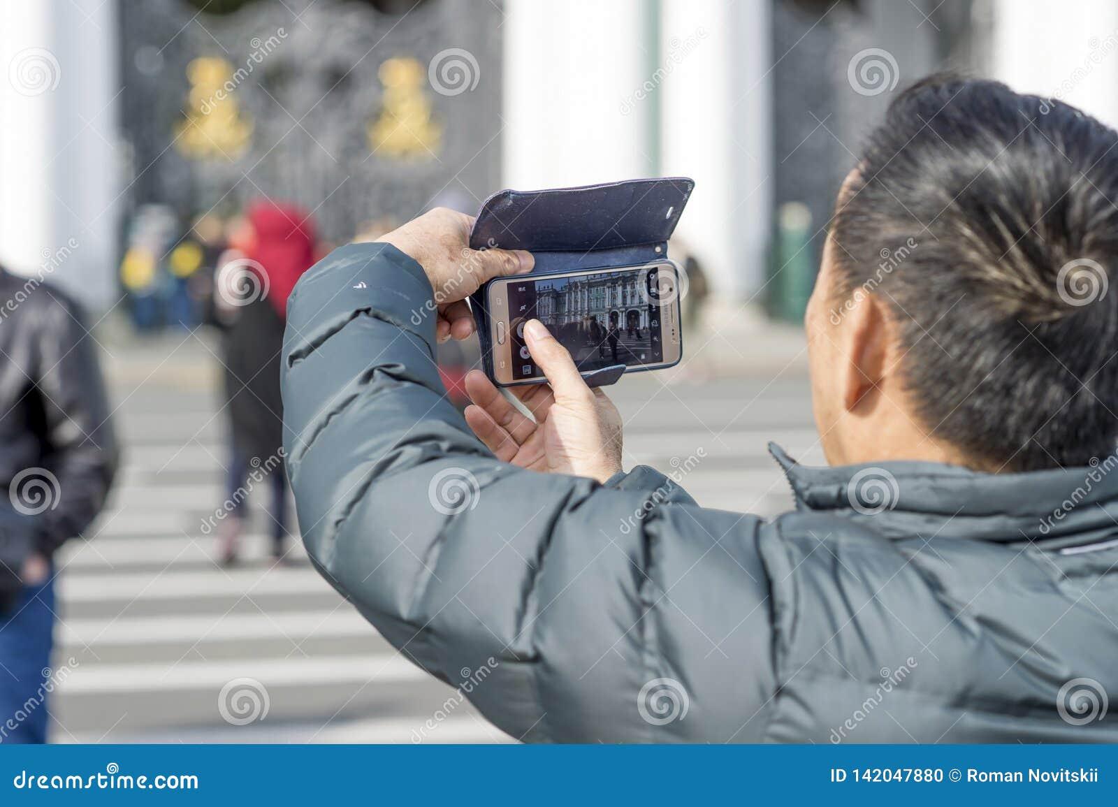 Un turista del hombre de las fotografías asiáticas del aspecto en el cuadrado del palacio de St Petersburg, Rusia, septiembre de