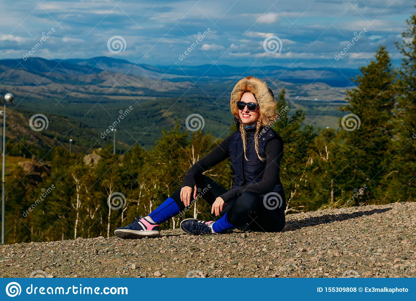 Un turista femenino sonriente joven en las montañas se sienta en la tierra