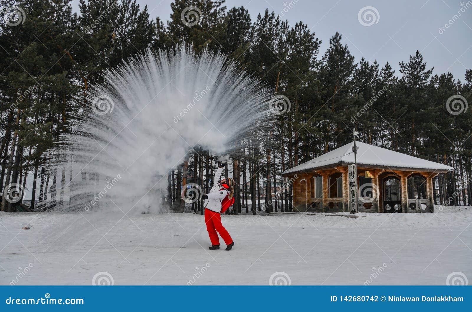 Un turista que lanza la agua caliente en el parque del invierno