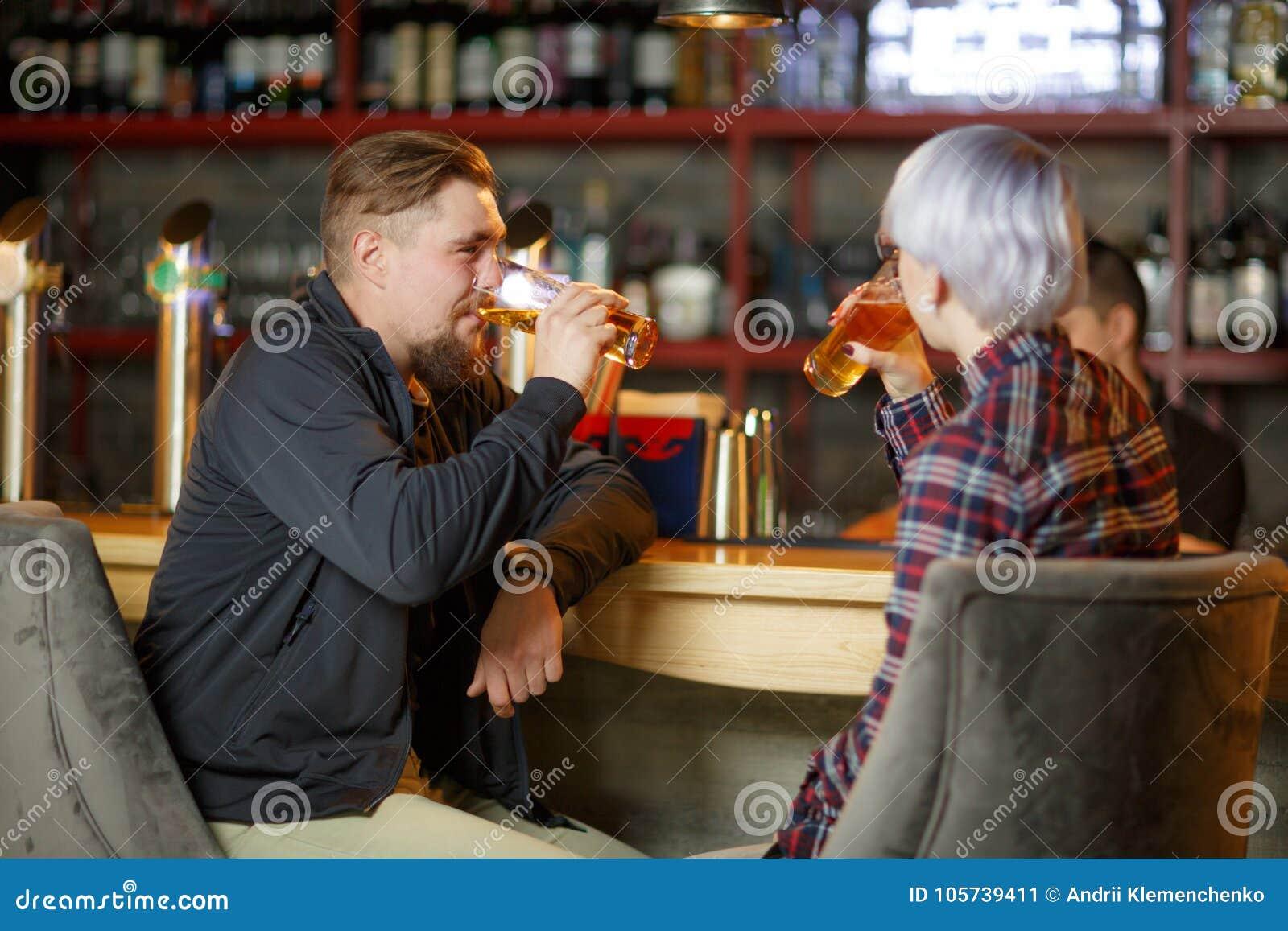Un type avec une barbe et une fille avec les cheveux blonds courts, se reposant dans une barre et une bière potable indoors
