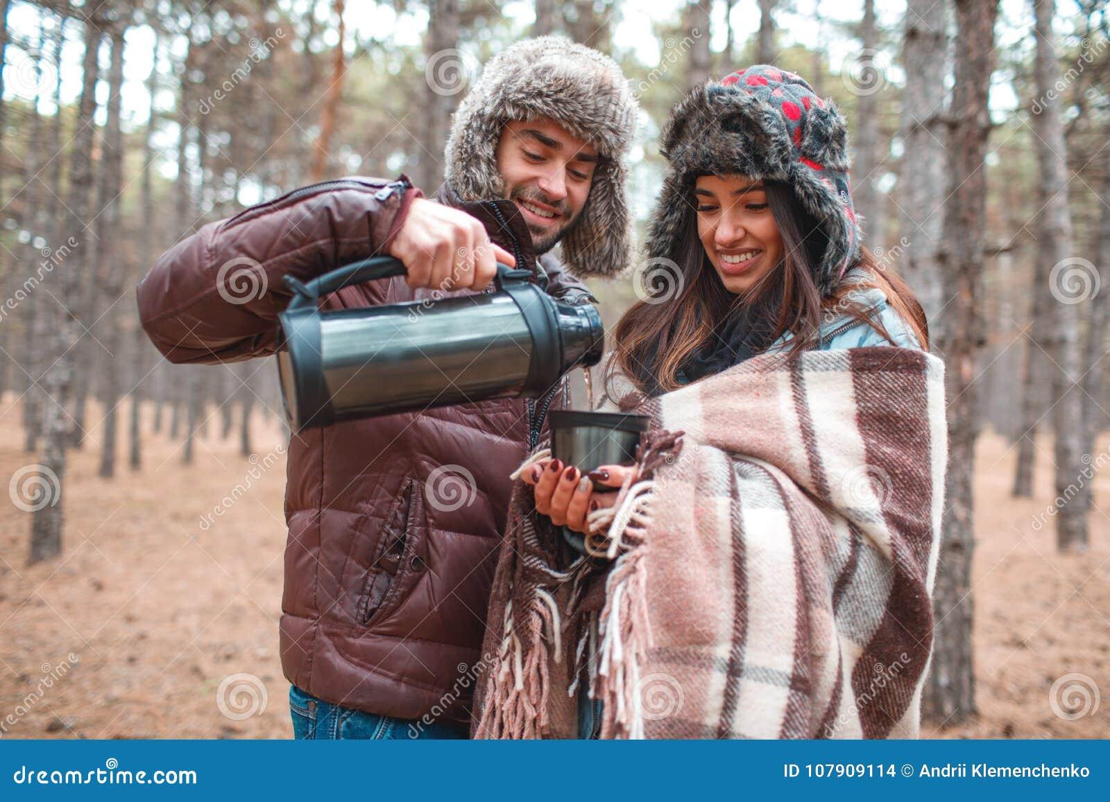 Un type verse le thé chaud pour une fille d un thermos dans une tasse dans la forêt d automne